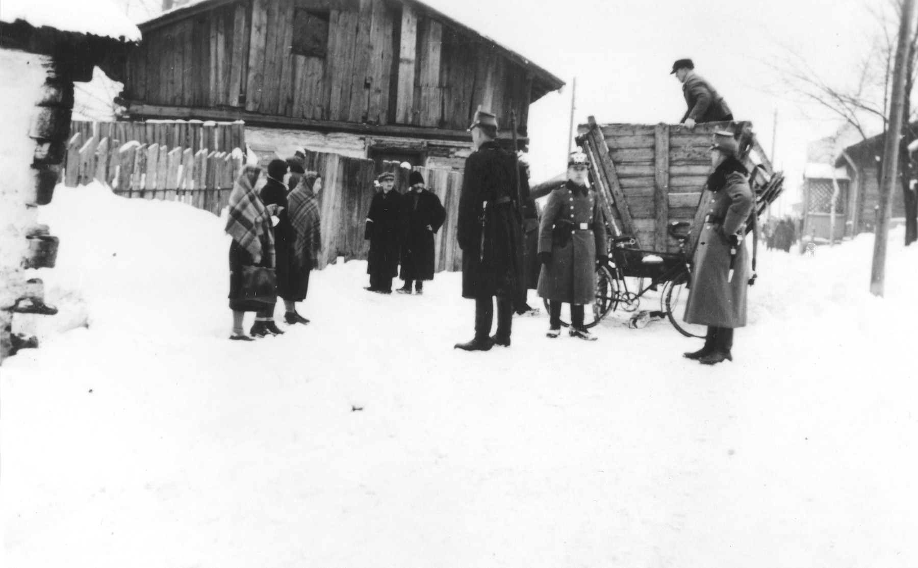 German police stop a group of Jews on a snow covered street in the Zawiercie ghetto.