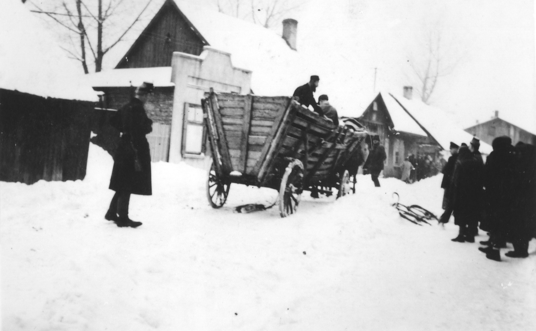 Jews drive a wagon along a snow covered street in the Zawiercie ghetto.