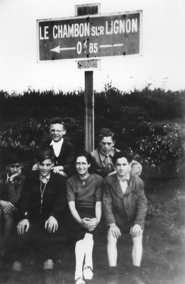 Juliette Usach and four boys sit beneath a sign directing the way to Le Chambon-sur-Lignon.