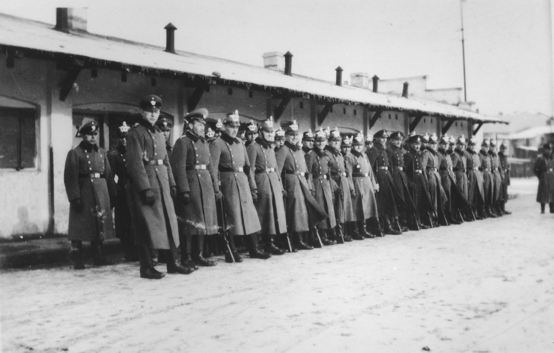 German police stand in formation in Zawiercie.   New Market Place in front of the trade pavillion.  Mainly butcher shops and other shops owned by Jews before the war.