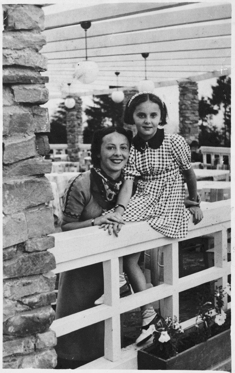 A woman and her daughter pose on the railing of a porch in prewar Poland.  Pictured are Ada and Rina Altbeker.