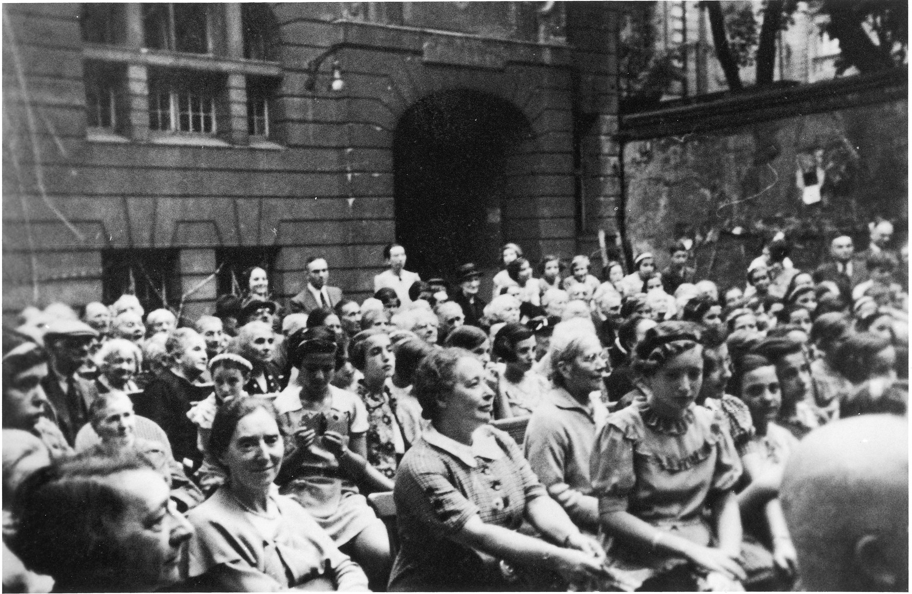 "Audience in the school yard of the Jewish school Grosse Hamburger Strasse during a performance of ""Max and Moritz"", a humorous poem by Wilhelm Busch.  People in the first row, from the left: Elisabeth Lasch (art teacher), Klara Heilmann (literature and French teacher), Mrs. Friedlaender (home room teacher), [girl with an hairband], Karla Ruelf (student, later Caroline Fierst). In the back between the two ladies: Mr Lipski (teacher). The man all the way to the right: Dr. Fritz Wiener. The elderly people in the audience are from the old age home (next to the school), the others are students."