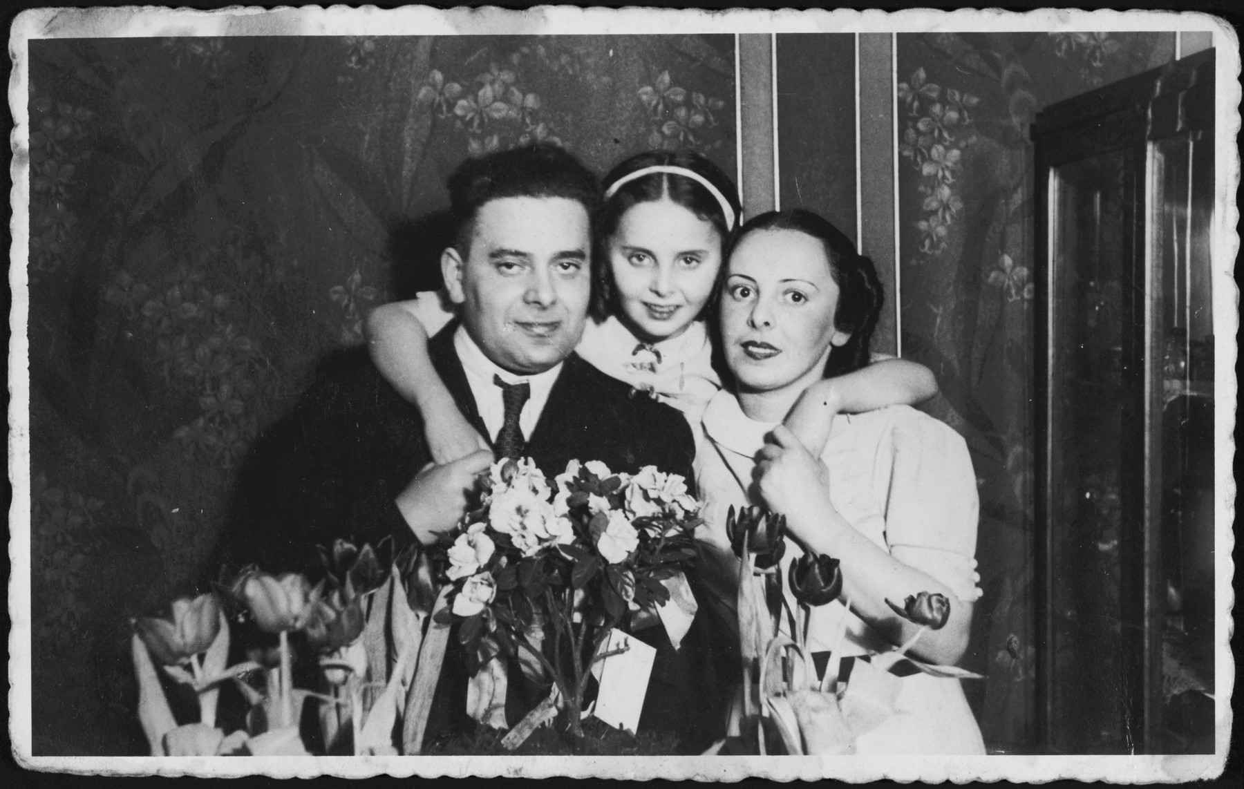 A young girl poses between her parents surrounded by flowers during their 10th anniversary party.  Pictured are Josef, Rina and Ada Altbeker.