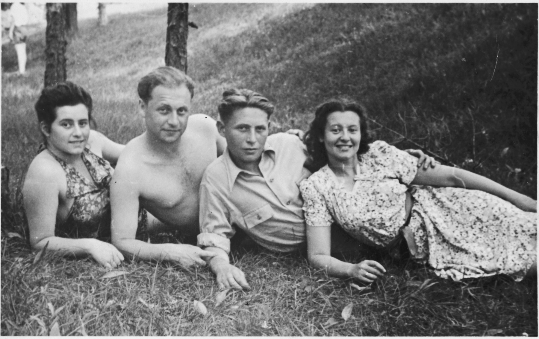 Four Jewish displaced persons lounge at the bottom of a grassy field.  Pictured are Dr. Genishevitz (second from left), his wife Ellis (far right), and two of their friends.   Dr. Genishevitz, a partisan, studied dentistry for four years in Germany before becoming accredited and immigrating to the United States. He said he wanted to avenge the German who had killed his father, and he managed to do so.
