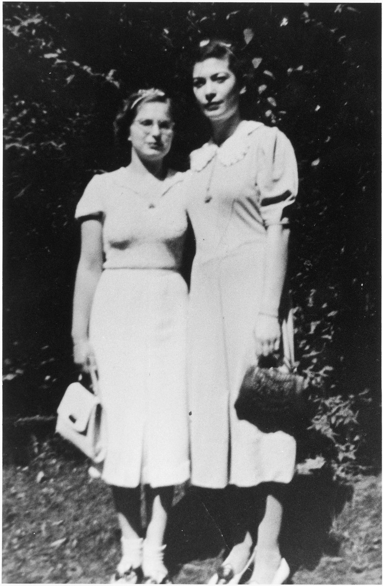 Portrait of Marianne Prager (left) and Inge Gerson (later Berner) standing close together in white dresses with handbags.