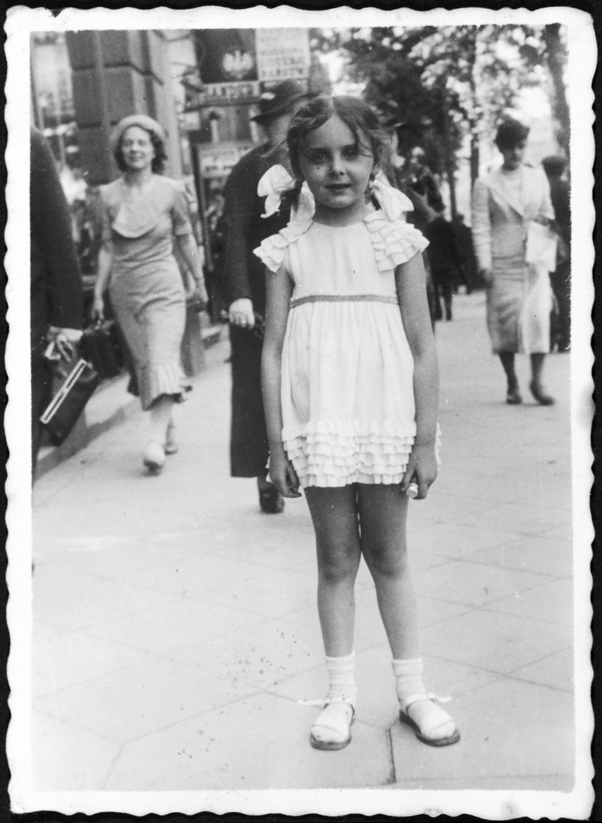 A young Jewish girl poses on a street in prewar Poland.  Pictured is Rina Altbeker.