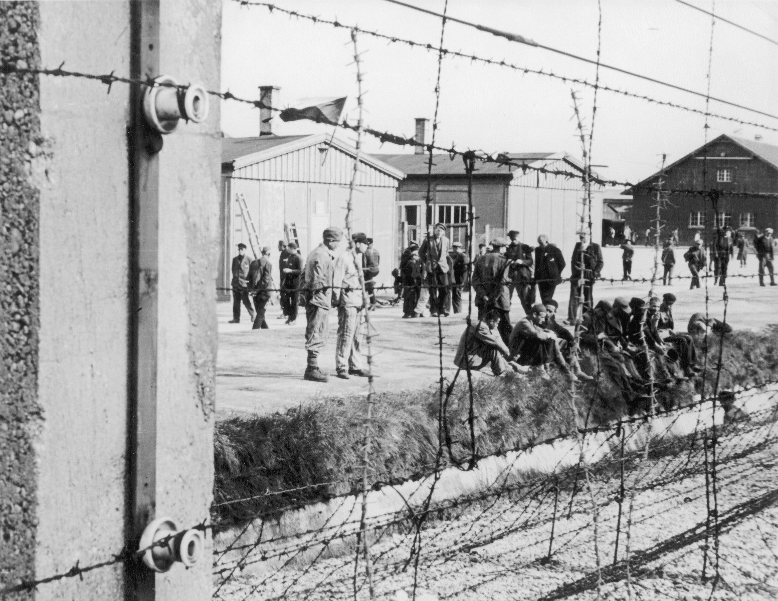 Survivors of the Dachau concentration camp rest alongside the surrounding moat behind a barbed wire fence.