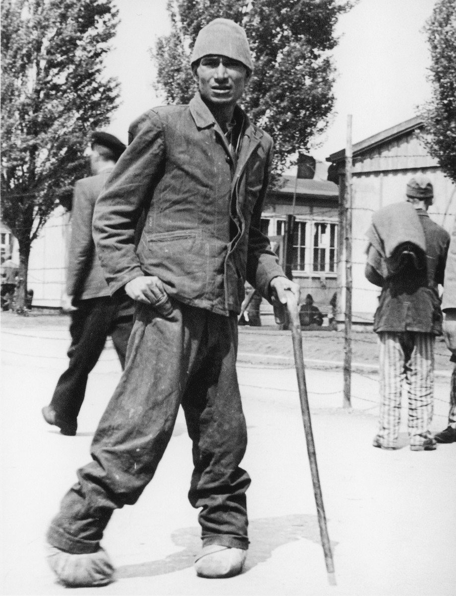 Close-up portrait of a survivor of the Dachau concentration camp with a cane.