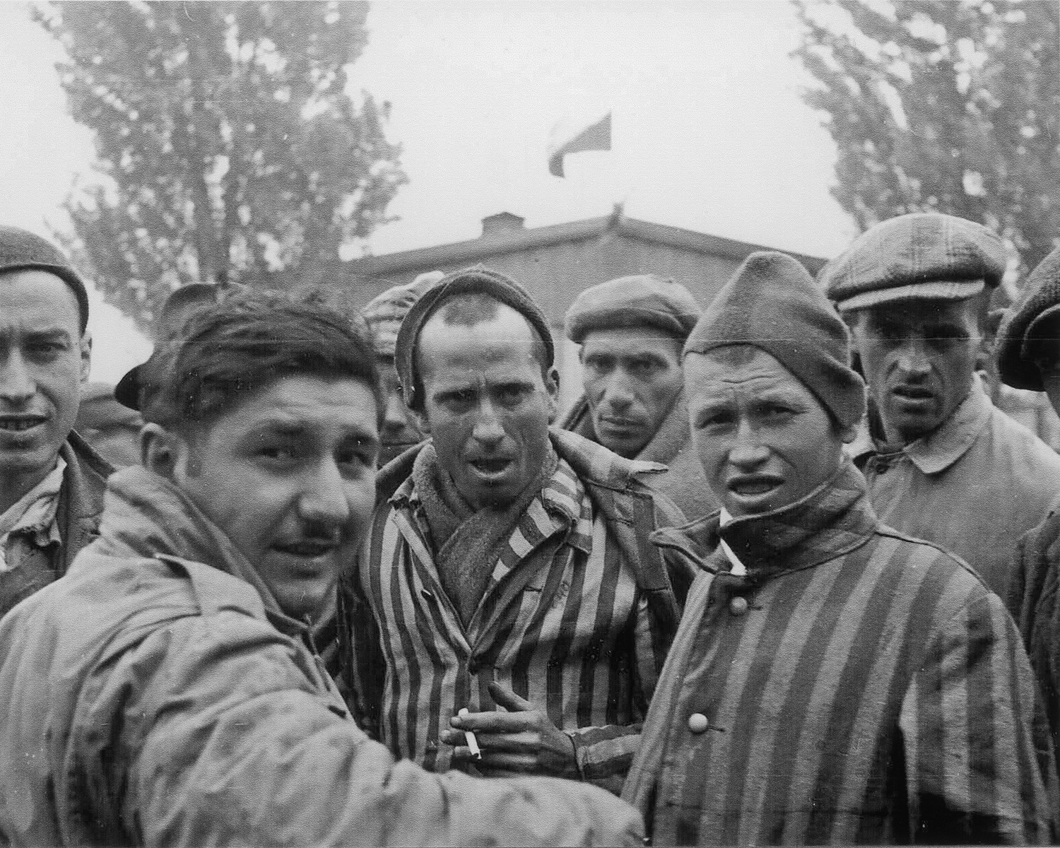 Close-up portrait of survivors of the Dachau concentration camp, one of whom is holding a cigarette.