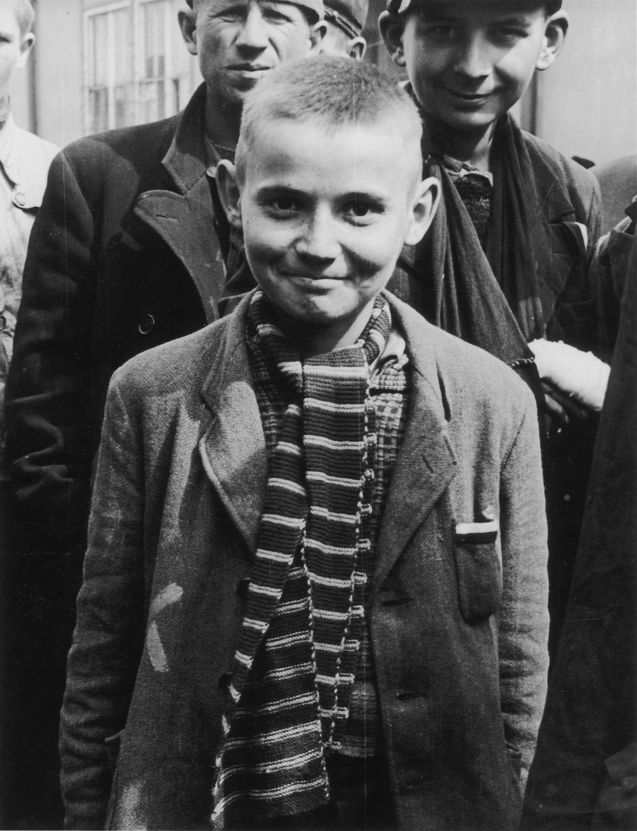 Close-up portrait of a child survivor of the Dachau concentration camp wearing a knit scarf.