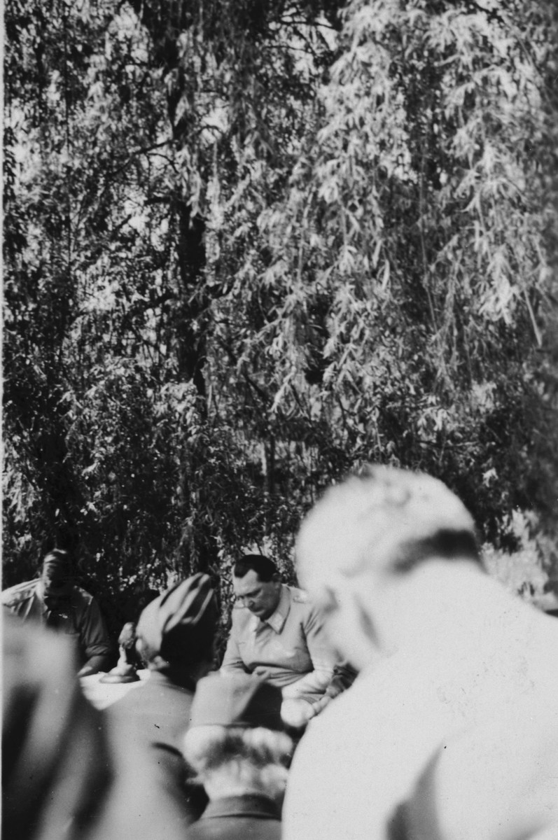 "Herman Goering speaks to American servicemen following his capture.  American prosecutors later criticized the Army for the lax treatment they afforded him.  The original caption [partially blurred] reads ""Goering sweating out the inquisition.  He 'squeeled' to [obscured]  his bull-like neck."""