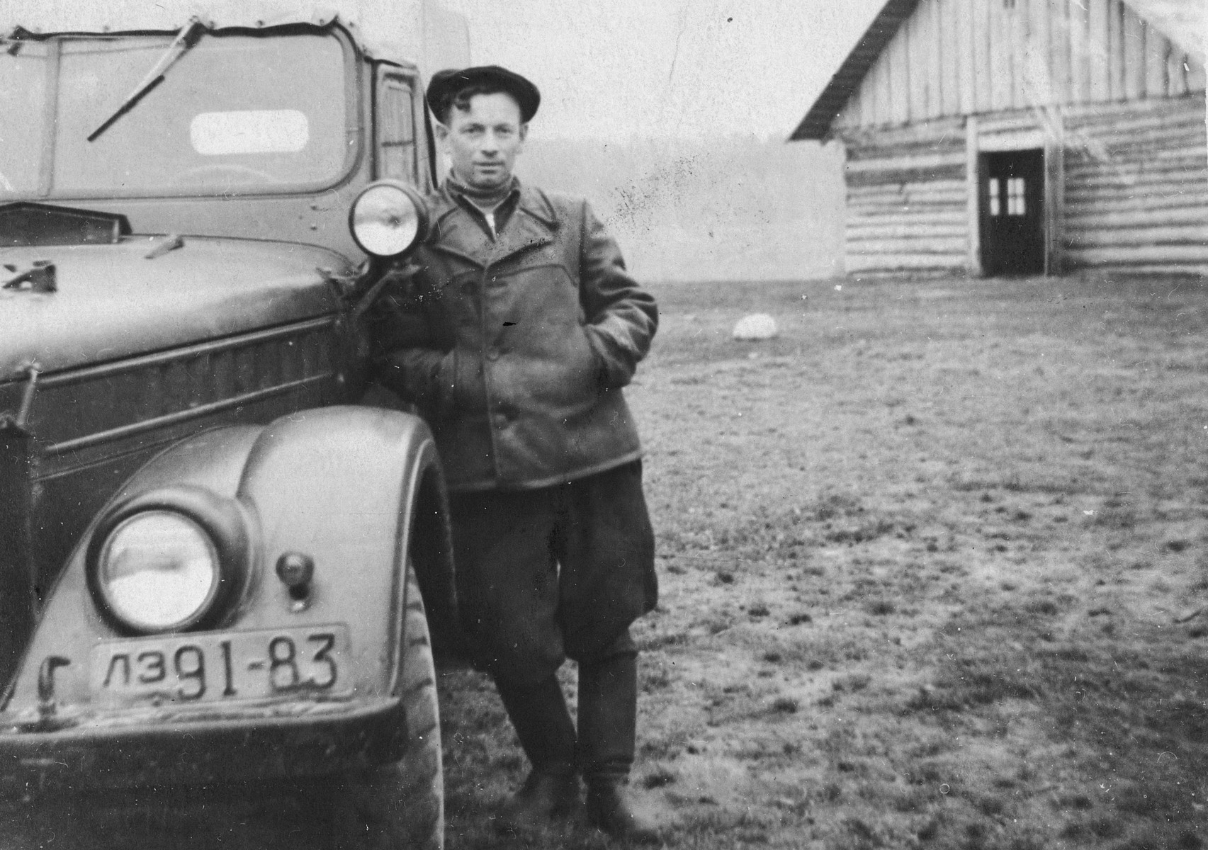 A young Jewish man leans against an automobile with a Russian license plate.  Pictured is Moishe Nodel, the husband of Niusia Gordon.