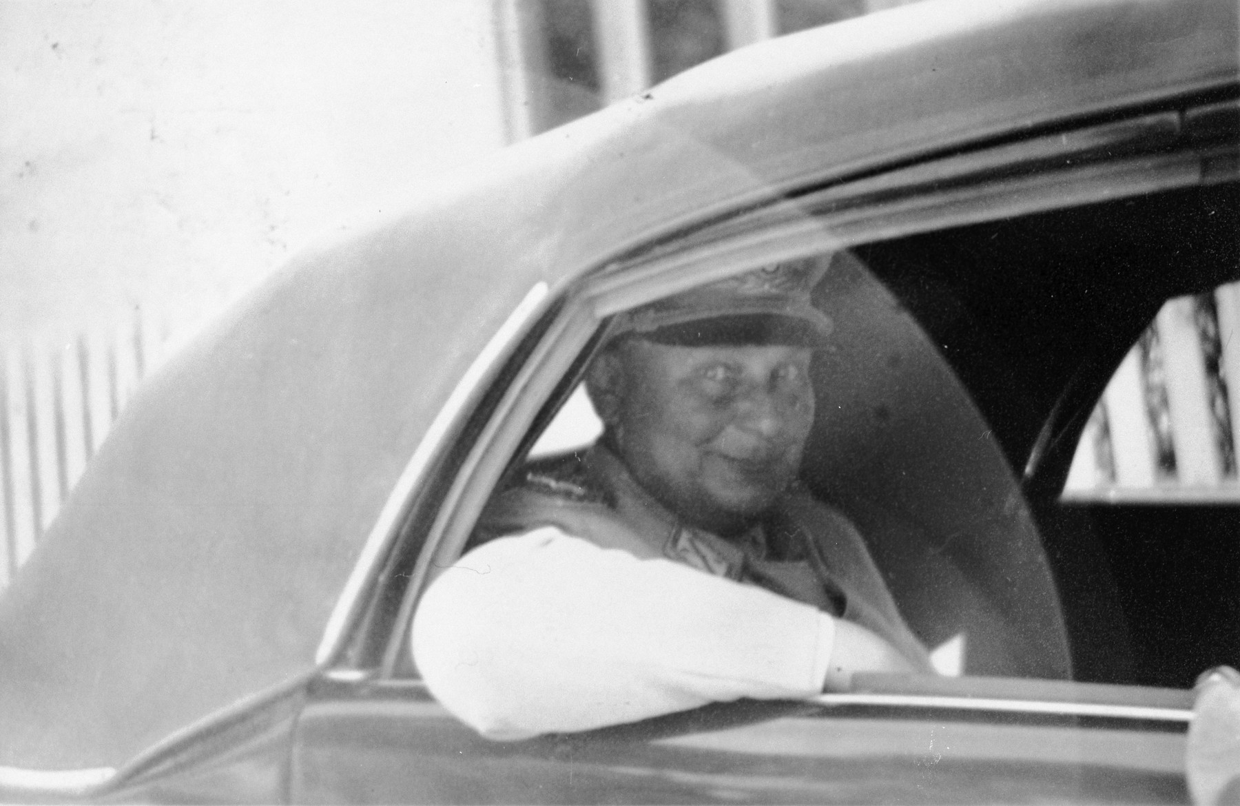 "Herman Goering is driven away in an automobile following his capture.    The original caption [partially blurred] reads ""Falstaff Goering being escorted by Yanks.  His smile has somehow vanished.  Note conspicuous absence of medals.  [rest obscured..]"""