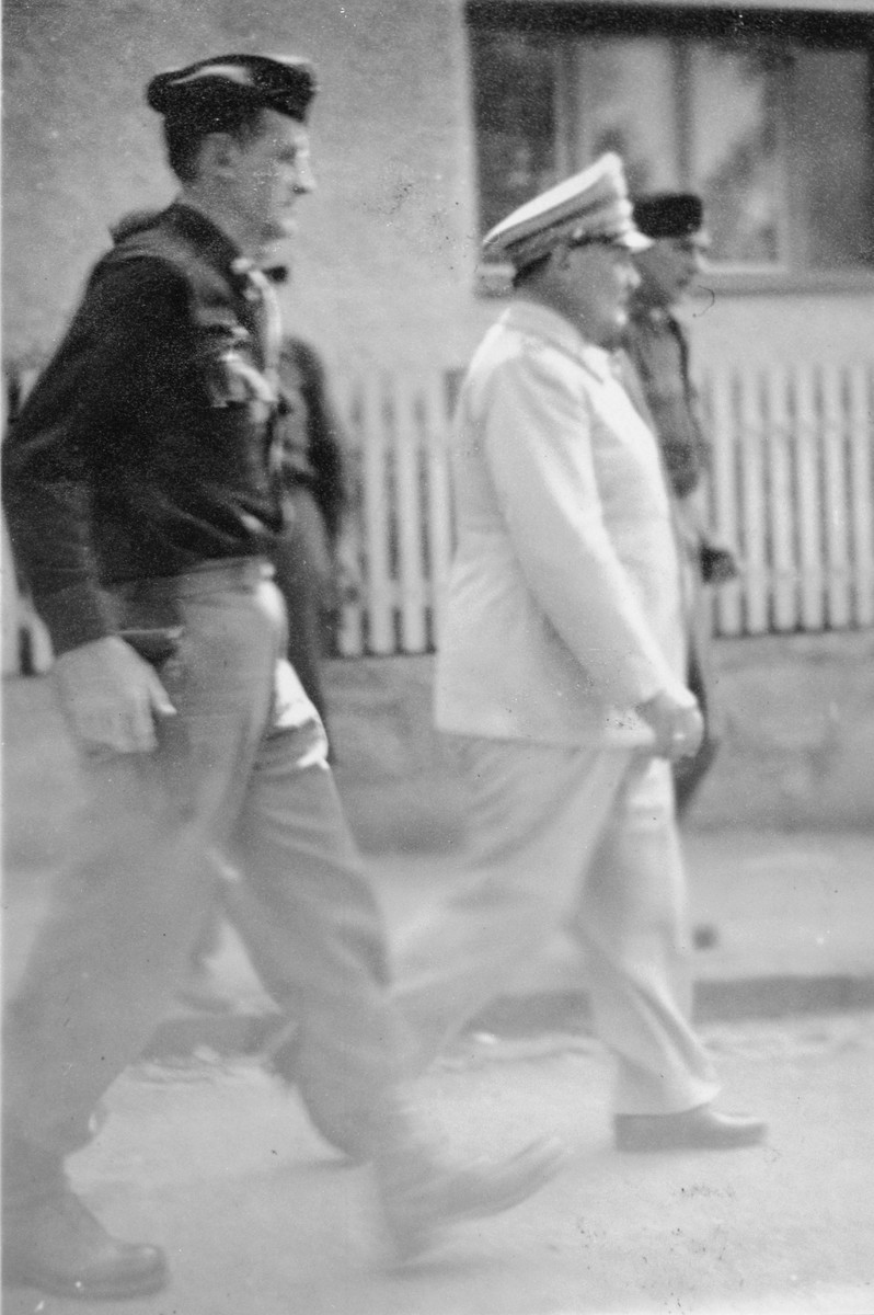 "Herman Goering is escorted by an American serviceman following his capture.    The original caption [partially blurred] reads ""Falstaff Goering is as ugly as he looks.  [Note the] sickeningly ingratiating smile -- It won't save him. """