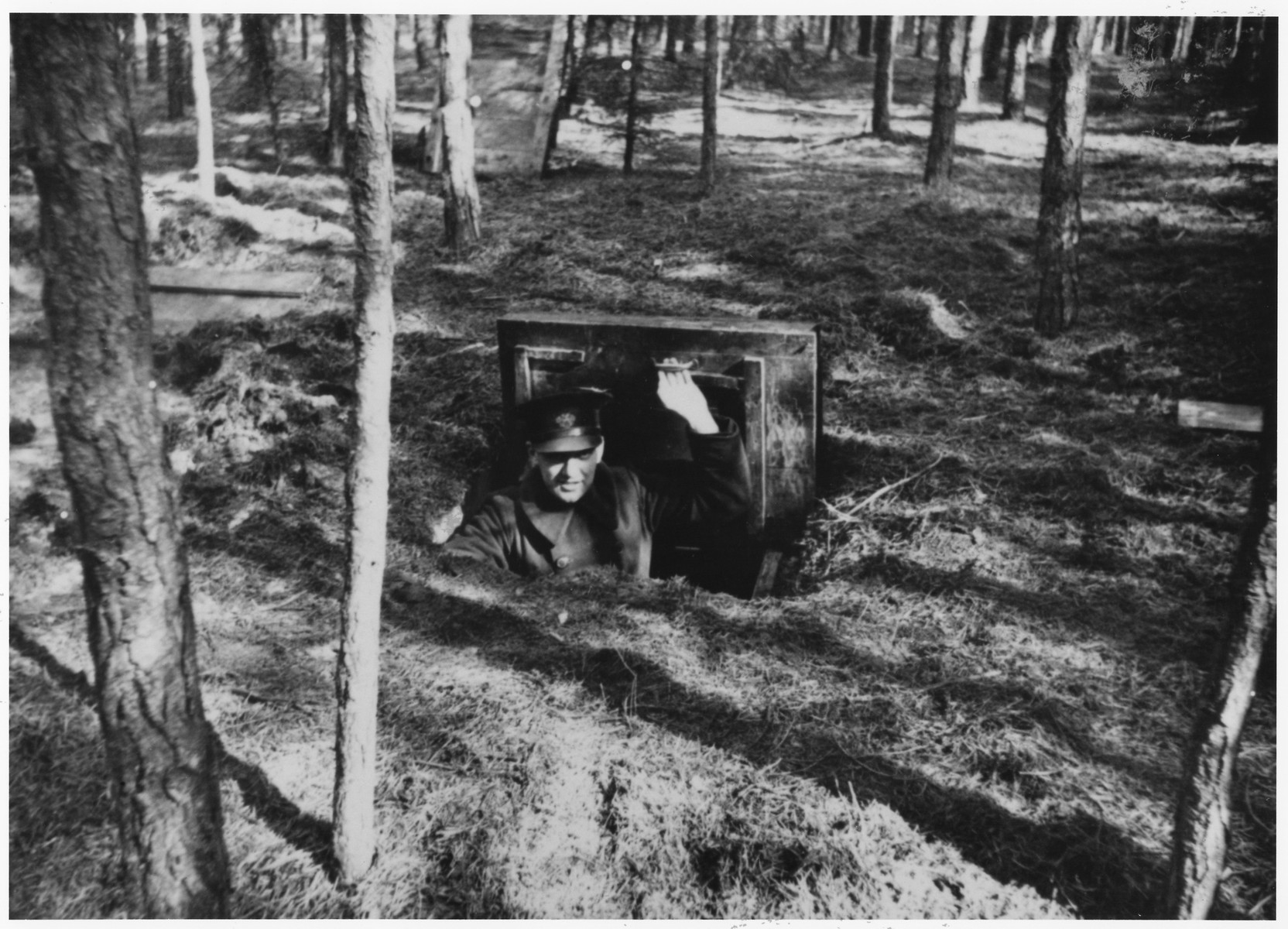 A Dutch policeman looks out the hatch of a small bunker that served as a hiding place for Dutch Jews in the Eibergen region in 1942-1943.  The bunker was discovered by the Germans one day before this photograph was taken.  The bunker was, in actuality, a prefabricated hut that was ordered by two Jewish brothers, Abraham and Herman Maas from Eibergen.  It was delivered in sections to a site in the Hoones Forest outside Eibergen.  The Maas brothers got permission from the manager of the privately-owned forest to build a subterranean hiding place for themselves.  Two sympathetic non-Jews conveyed the materials, dug the hole and assembled the shelter, which had two rooms and a crude stove.  Initially, only the brothers hid there, but as times grew more desperate, 23 Jews were concealed in the bunker.  On March 27, 1943 a Dutch informer led Germans to the site.  All 23 were arrested and sent to Westerbork.  From there they were deported to Sobibor and killed.  After the war the informer was identified as E. Heijink and tried as a collaborator.  The photographer was a Dutchman, who was ordered to take pictures of the bunker the day after the Jews were captured.  He made an extra set of prints, which he kept secretly, and made available to resisters and surviving Jews after the liberation.  The policeman posed inside the bunker in order to better convey its size.