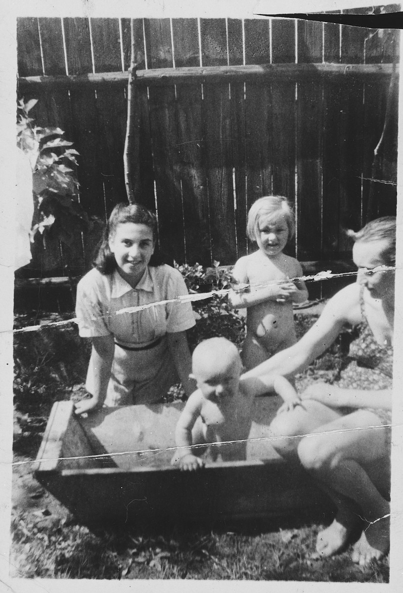 A twelve-year-old Jewish girl plays with her rescuer's family in their yard.  Pictured is Hetty Fisch and Anna Majercik and her two children.
