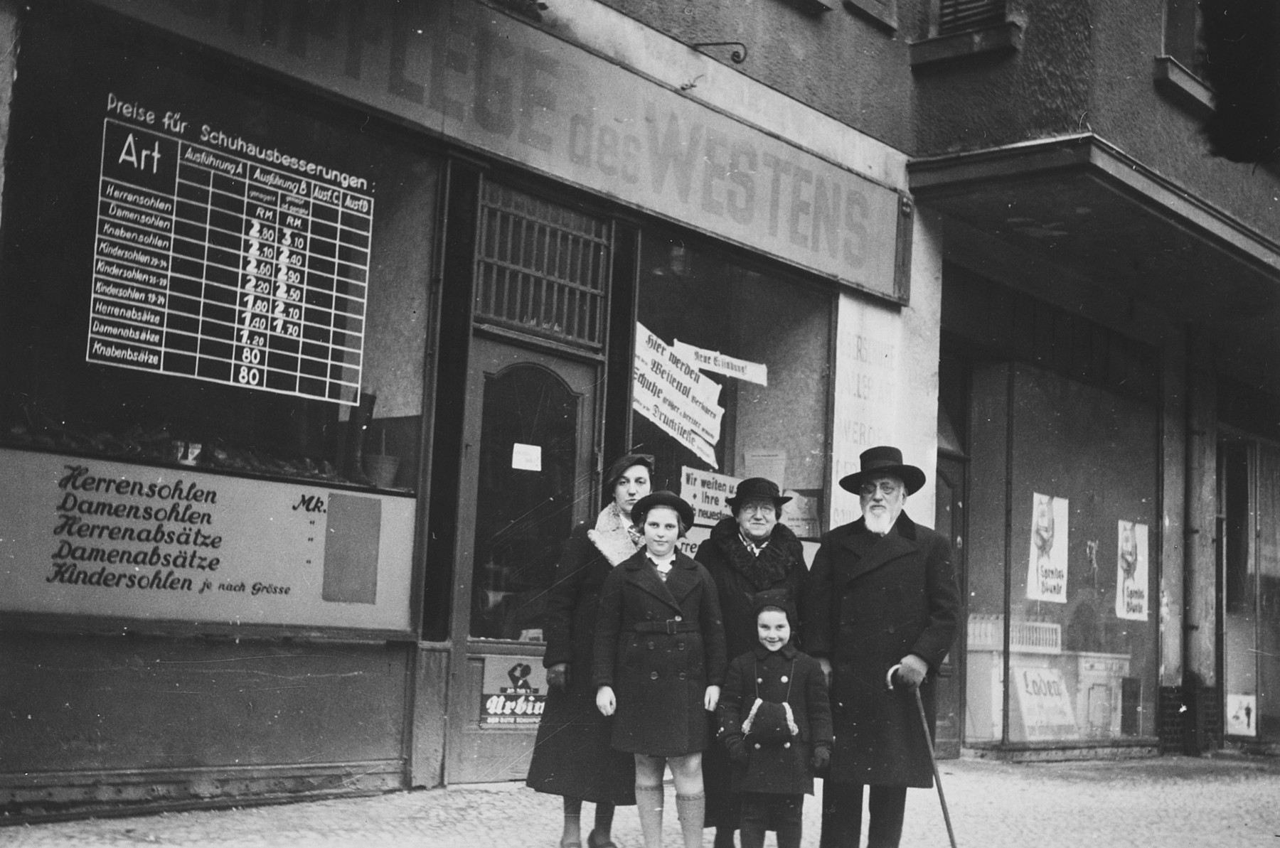 An extended Jewish family poses in front of a store plastered with posters in Berlin.  Pictured are Hetty Fisch, her grandparents and cousins.