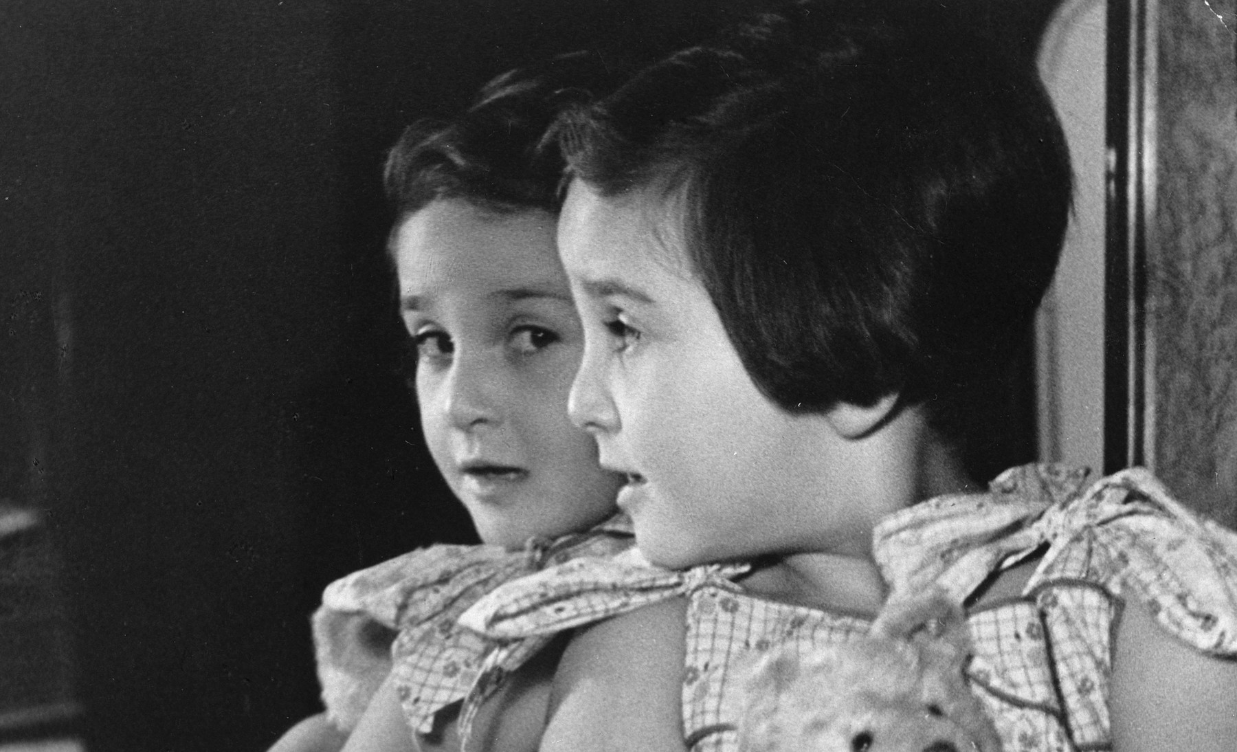 A young Czech-Jewish girl looks at herself in the mirror.  Pictured is Hetty Fisch.