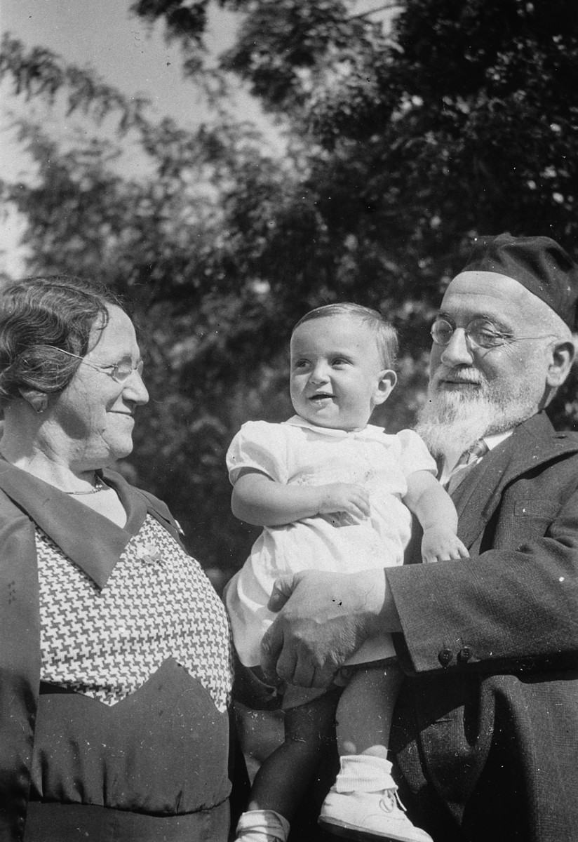 An orthodox Jewish couple poses with their baby granddaughter.  Pictured are Hetty Fisch and her grandparents.