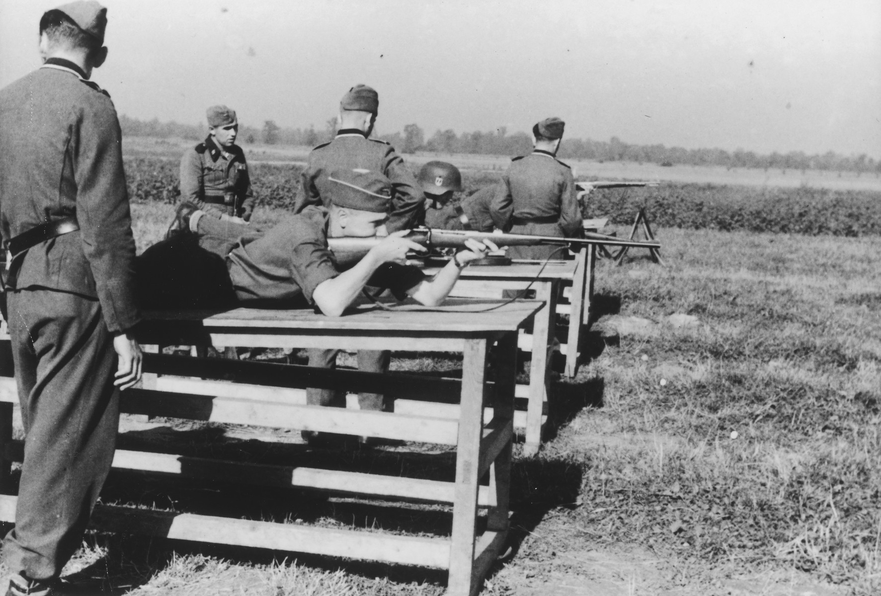 "Karl Hoecker shoots his rifle while lying on a wooden table during target practice.   The original caption reads ""Der Schuss wurde eine 12"" (the shot was a 12)."