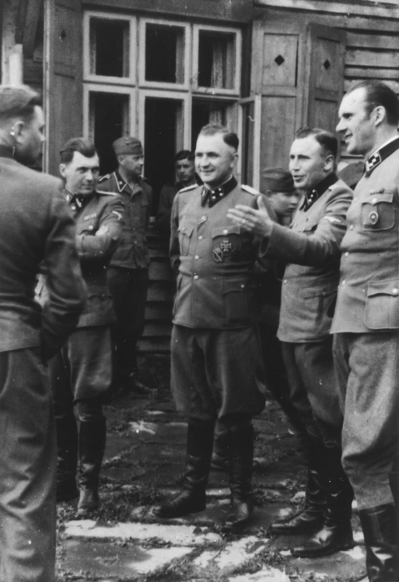 Nazi officers stand on a terrace of Solahuette, the SS retreat outside of Auschwitz.  Pictured on the far left is Josef Kramer (back to camera) and Dr. Josef Mengele, Commandant Richard Baer, his adjutant Karl Hoecker and Walter Schmidetzki.  [Based on the officers visiting Solahutte, we surmise that the photographs were taken to honor Rudolf Hoess who completed his tenure as garrison senior on July 29.]
