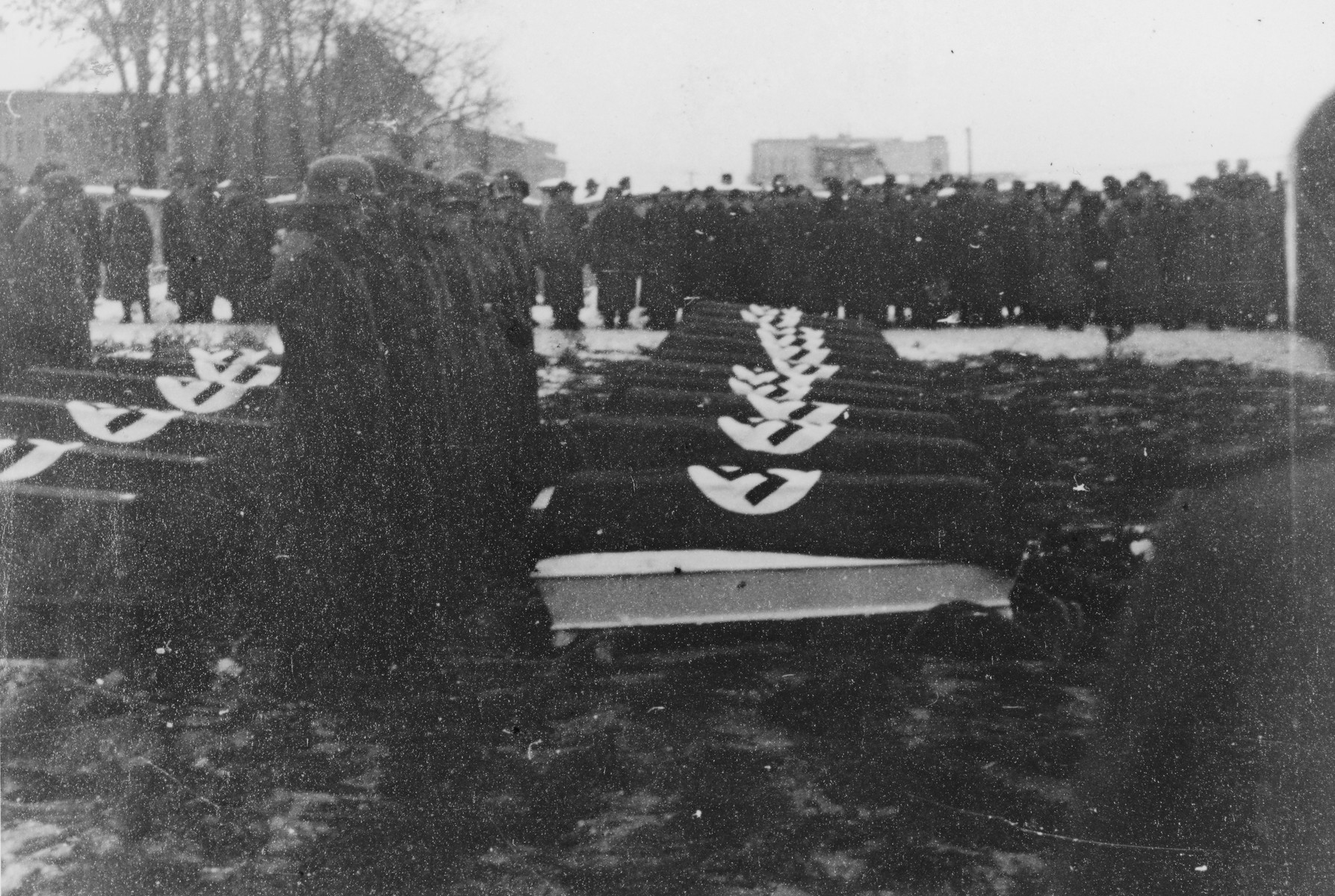 "German troops stand at attention alongside a row of coffins during a military funeral near Auschwitz.  The original caption reads ""Beisetzung von SS Kameraden nach einem Terrorangriff.""  (Burying our SS comrades from a terror attack.)  [This probably is the aftermath of the December 26 bombing based on the snow on the ground but it could also be September 13th bombing of IG Farben in which 15 SS men died in the SS residential blocks and 28 were seriously wounded.]"