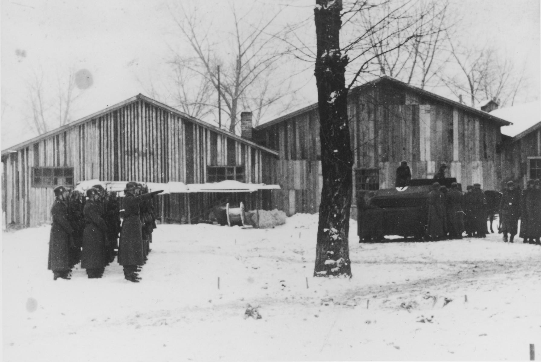"Three rows of German soldiers stand at attention and salute during a military funeral in Auschwitz.  The original caption reads ""Beisetzung von SS Kameraden nach einem Terrorangriff.""  (Burying our SS comrades from a terror attack.)  [This probably is the aftermath of the December 26 bombing based on the snow on the ground but it could also be September 13th bombing of IG Farben in which 15 SS men died in the SS residential blocks and 28 were seriously wounded.]"