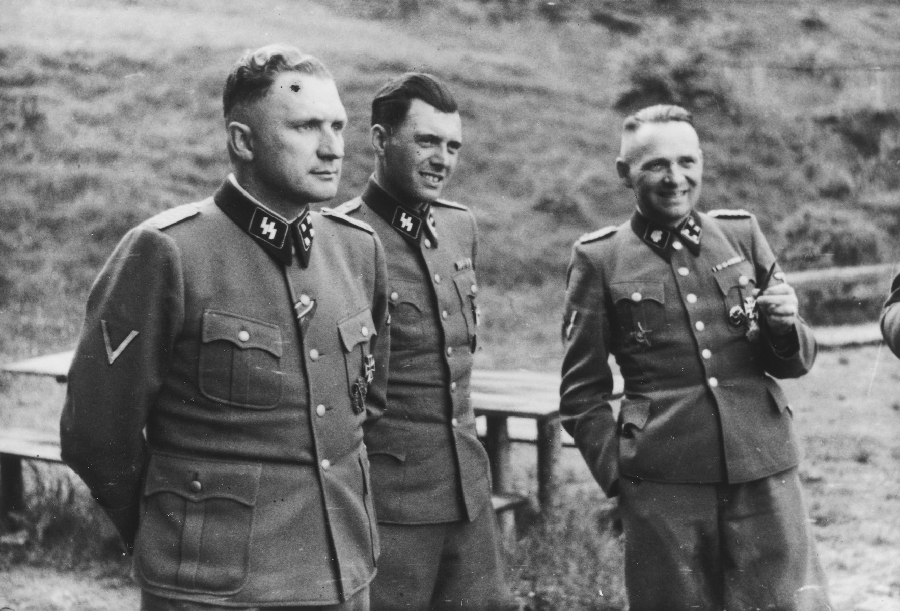 Three SS officers socialize on the grounds of the SS retreat of Solahuette outside of Auschwitz.  From left to right they are: Richard Baer (Commandant of Auschwitz), Dr. Josef Mengele and Rudolf Hoess (the former Auschwitz Commandant).   [Based on the officers visiting Solahutte, we surmise that the photographs were taken to honor Rudolf Hoess who completed his tenure as garrison senior on July 29.]