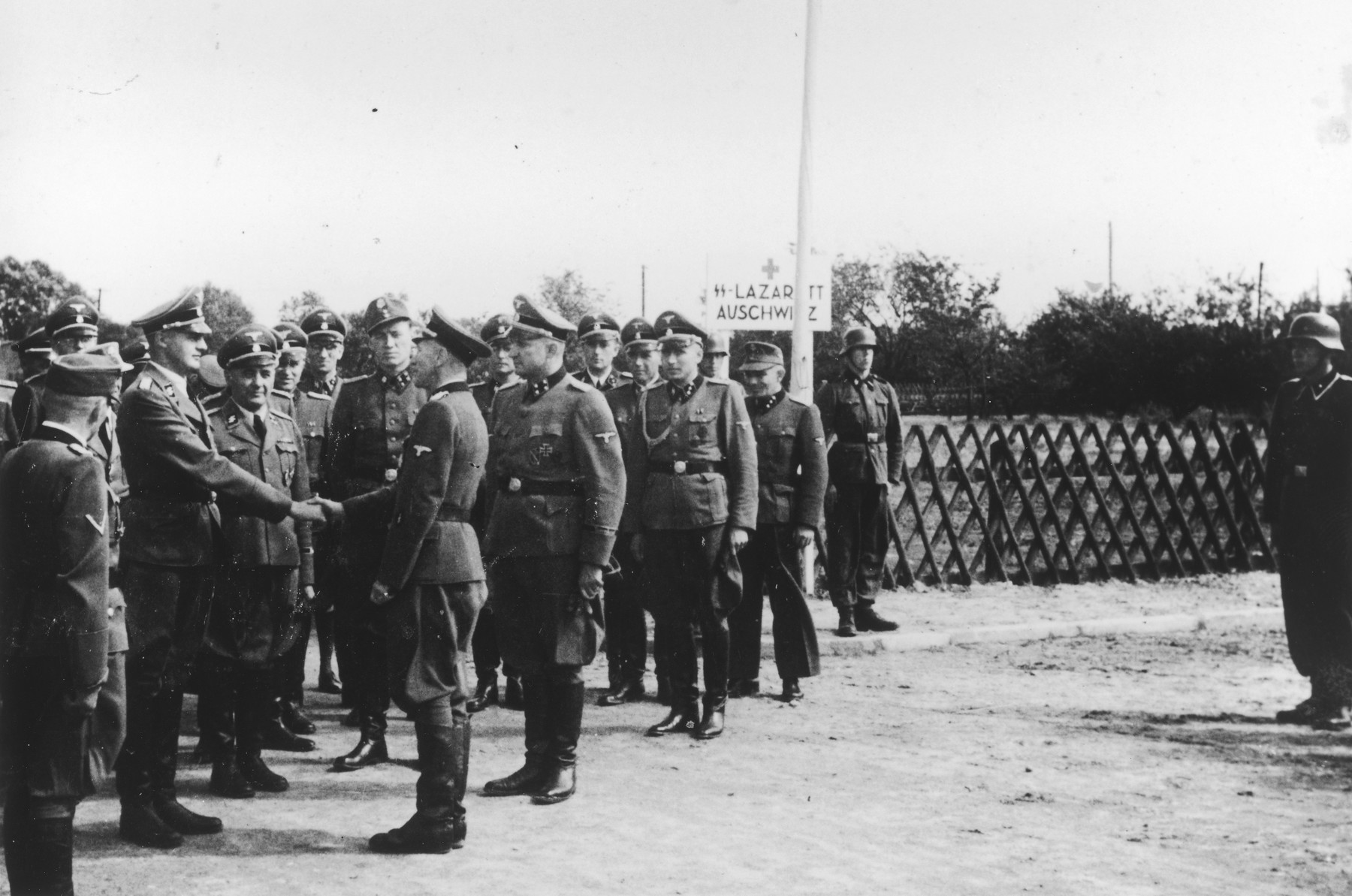 """Dr. Lolling shakes the hand of Dr. Eduard Wirths during the dedication of the new SS hospital in Auschwitz.  The original caption reads """"Die Ubergabe"""" (the handover).  The ceremony marks the transfer of documents and authority from the construction department to the camp upon completion of the project.  Next to Dr. Wirths is Karl Bischoff, head of construction in Silesia. Standing in the background, between the doctors, (is probably August Harbaum, adjutant to Richard Gluecks).  Standing on the left with his back to the camera is Rudolf Hoess.  Dr. Wirths also received his promotion to Sturmbannfuehrer and decorated with the War Service Cross 1st Class at the same time and this might be what is being portrayed here."""