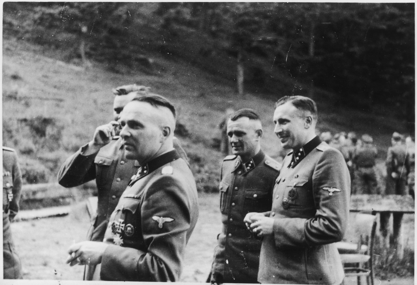 SS officers socialize on the grounds of the SS retreat Solahuette outside of Auschwitz.   From left to right they are: Rudolf Hoess, Josef Kramer (partially obscured behind him), Anton Thumann and Karl Hoecker.  [Based on the officers visiting Solahutte, we surmise that the photographs were taken to honor Rudolf Hoess who completed his tenure as garrison senior on July 29.]