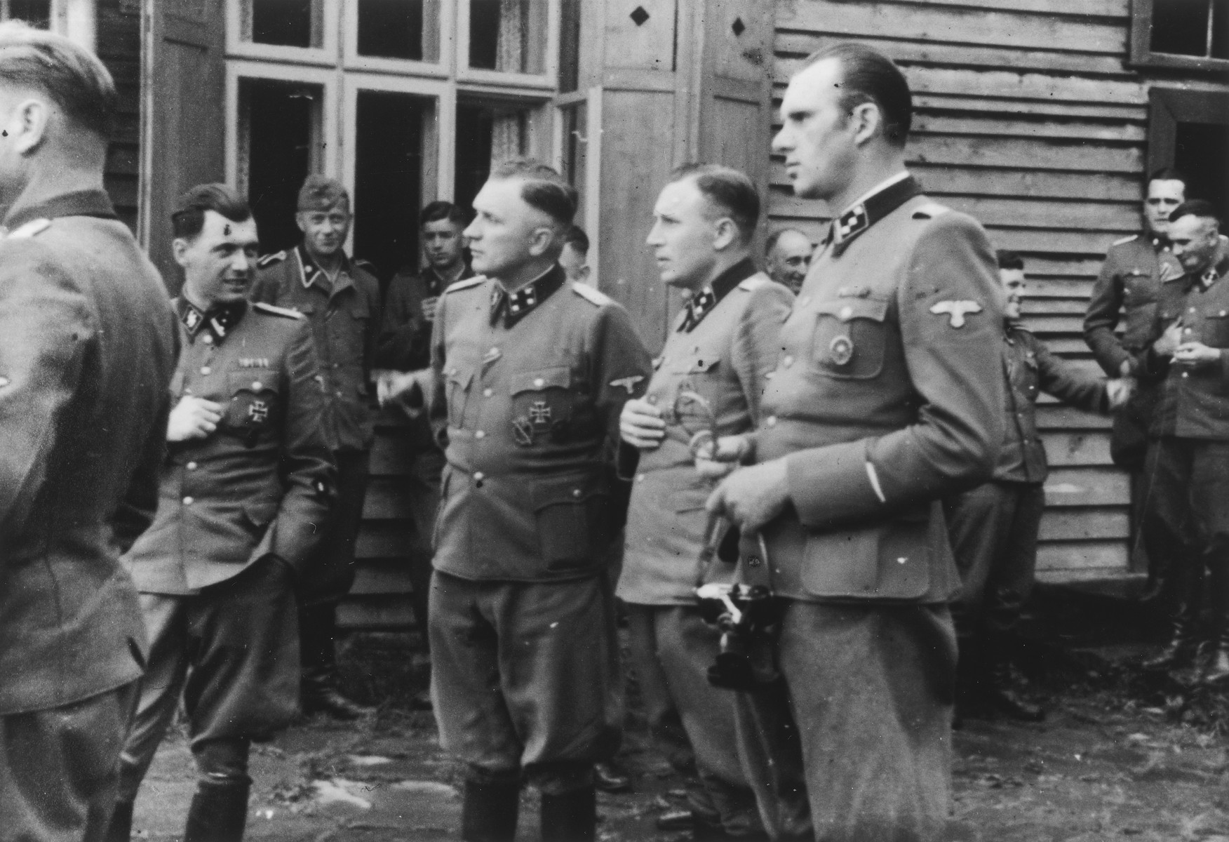 SS officers socialize at the SS retreat of Solahuette outside of Auschwitz.  From left to right they are: Josef Mengele, Richard Baer (Commandant of Auschwitz), Karl Hoecker (his adjutant) and Walter Schmidetzki (head of Kanada and later Aministrative Director of Monowitz). Konrad Wiegand, head of the Fahrbereitschaft (car and truck pool) is at the back right.  Pictured in the background between Hoecker and Schmidetzki is Herman Balthasar Philip Buch, who would become the kommandofuehrer of the sonderkommando around September 1, 1944, taking over from Otto Moll.  [Based on the officers visiting Solahutte, we surmise that the photographs were taken to honor Rudolf Hoess who completed his tenure as garrison senior on July 29.]