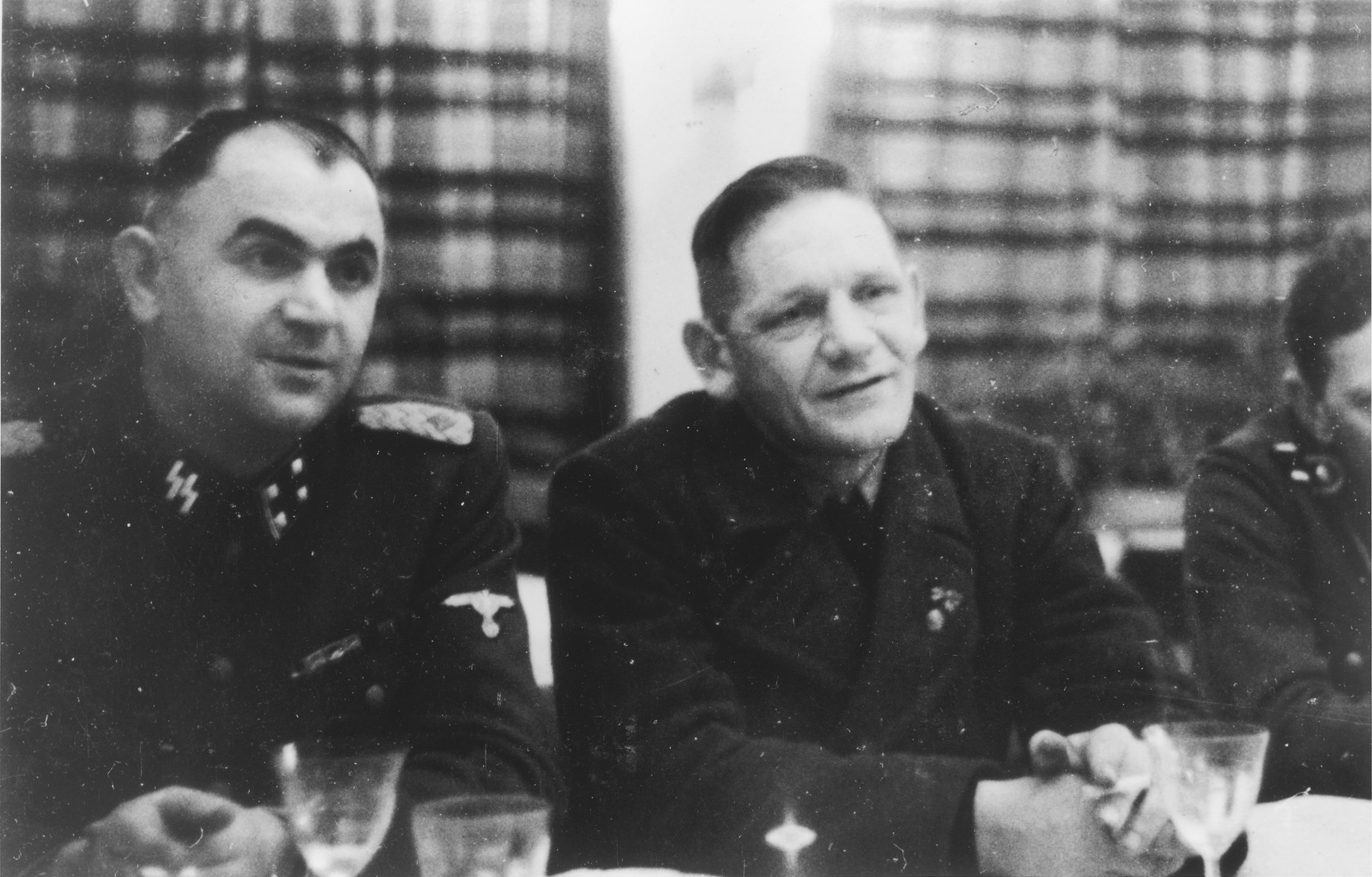 Two SS officers gather for drinks in a hunting lodge.  Pictured on the lett is Karl Moeckel.