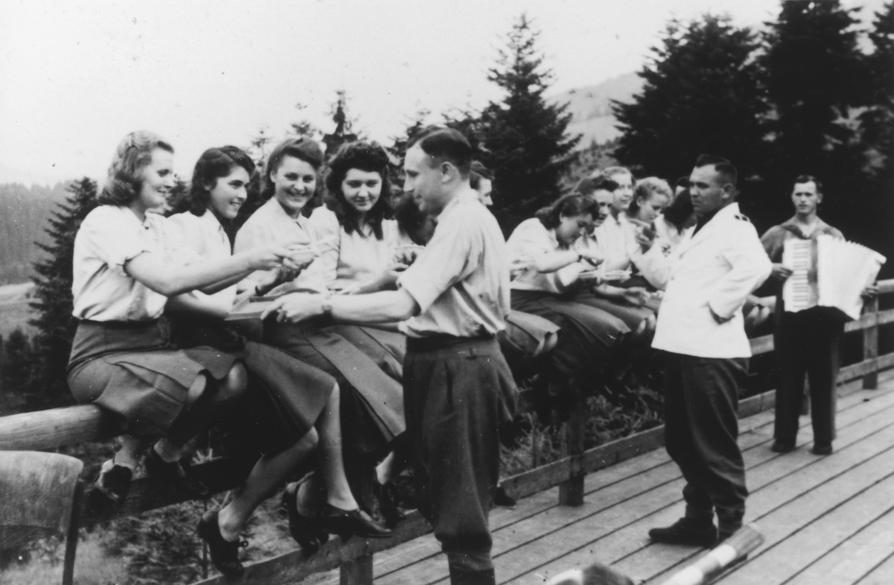 """Members of the SS Helferinnen (female auxiliaries) sit on a fence railing in Solahuette as Karl Hoecker passes out bowls of blueberries.  In the background is a man playing the accordion.   The original caption reads """"Hier gibt es Blaubeeren"""" (there are blueberries here)."""