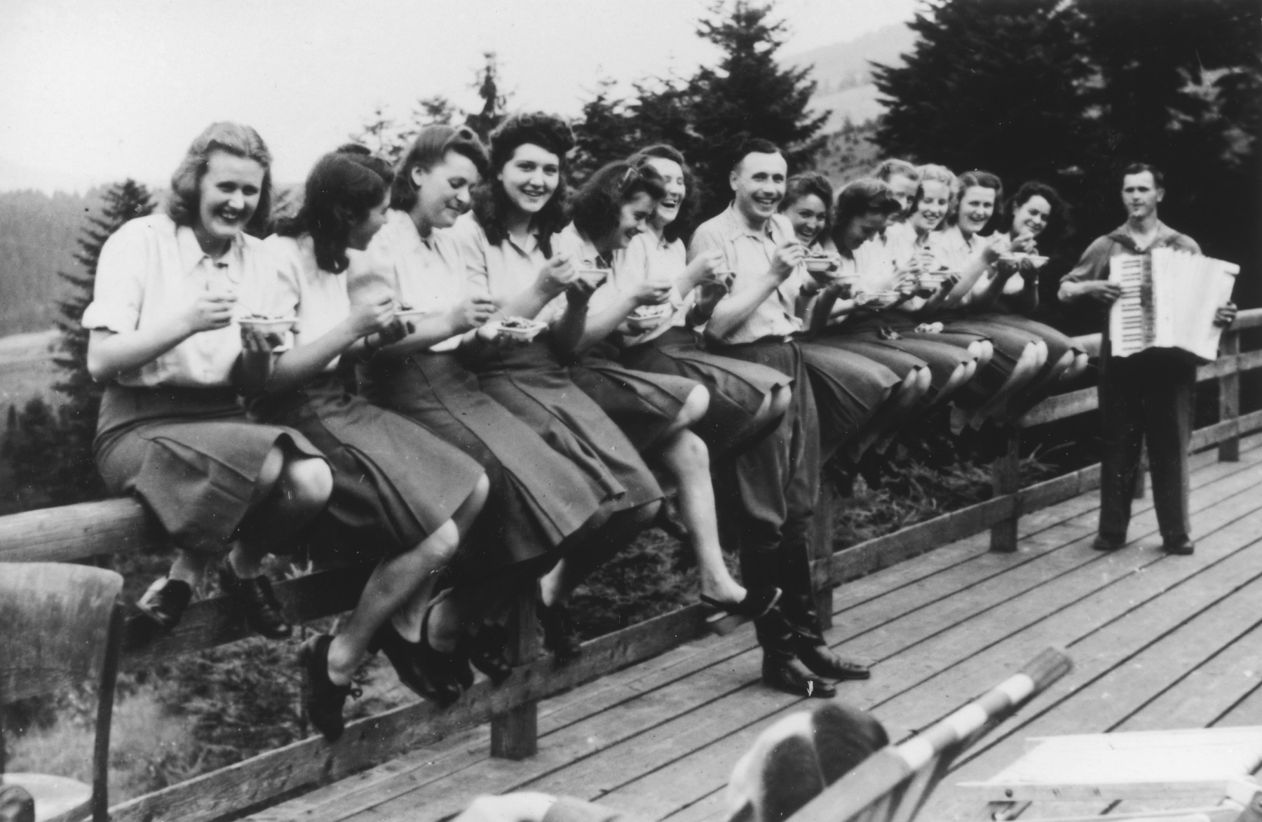 "Members of the SS Helferinnen (female auxiliaries) and SS officer Karl Hoecker sit on a fence railing in Solahuette eating bowls of blueberries.  In the background is a man playing the accordion.   The original caption reads ""Hier gibt es Blaubeeren"" (there are blueberries here)."