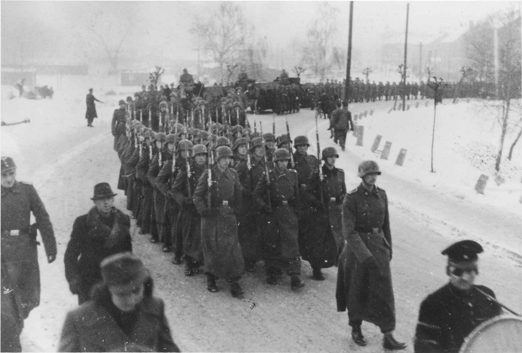 "Germans troops in three long columns march along with rifles shouldered during a military funeral near Auschwitz.  The original caption reads ""Beisetzung von SS Kameraden nach einem Terrorangriff.""  (Burying our SS comrades from a terror attack.)  [This probably is the aftermath of the December 26 bombing based on the snow on the ground but it could also be September 13th bombing of IG Farben in which 15 SS men died in the SS residential blocks and 28 were seriously wounded.]"