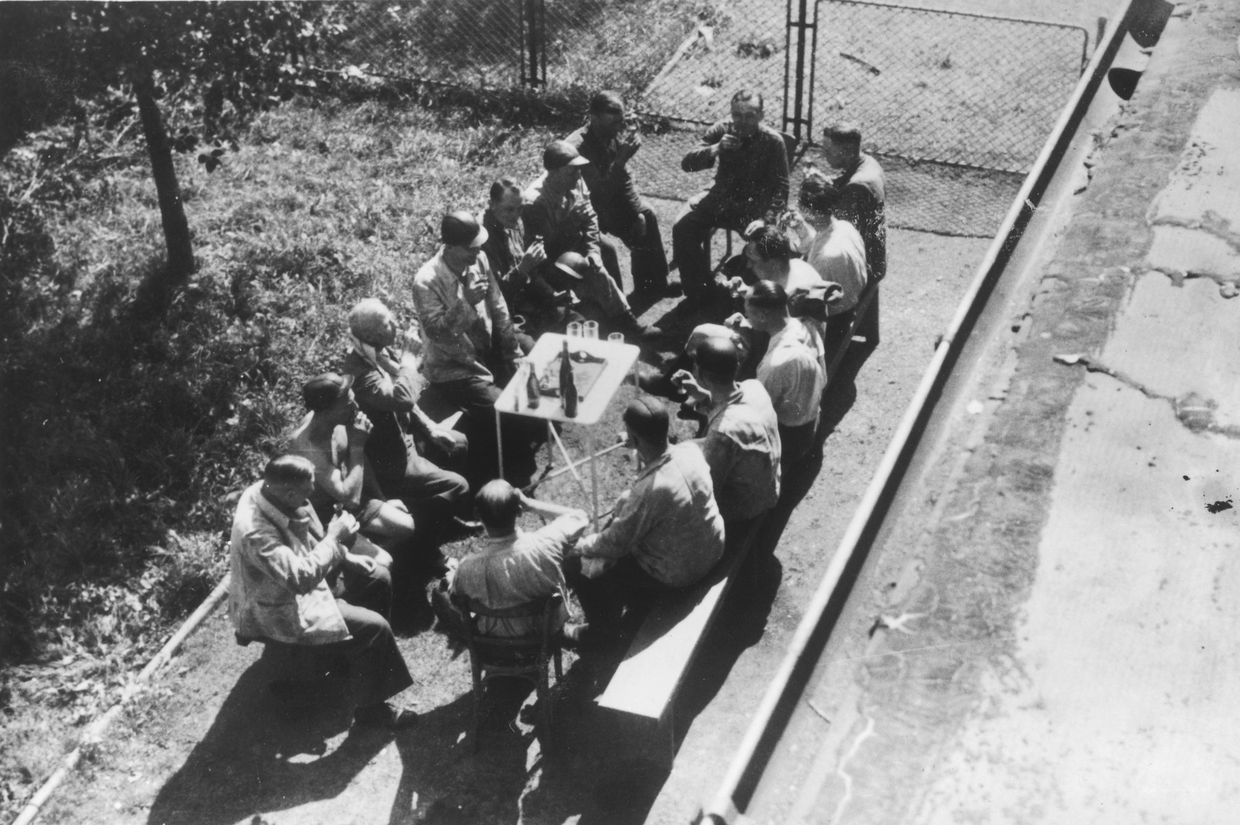 "Auschwitz personnel, including many physicians, enjoy drinks at an outdoor table drinking following a visit to a coal mine.  The original caption reads ""Nach der Ausfahrt"" (after the outing [exiting the mine])."