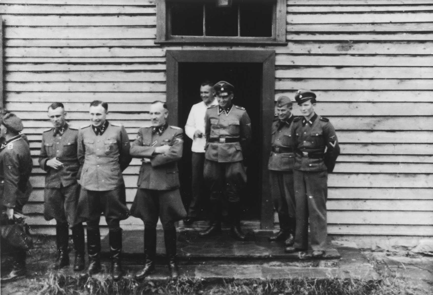 A group of Nazi officers stand in front of a building in Solahuette, the SS retreat outside of Auschwitz.  Pictured facing the camera, second from the left, is Karl Hoecker.  Next to him is SS-Obersturmführer Max Sell, between 1943 and 1945 first Arbeitseinsatzführer in Auschwitz and afterwards in Mittelbau-Dora.   [Based on the officers visiting Solahutte, we surmise that the photographs were taken to honor Rudolf Hoess who completed his tenure as garrison senior on July 29.]