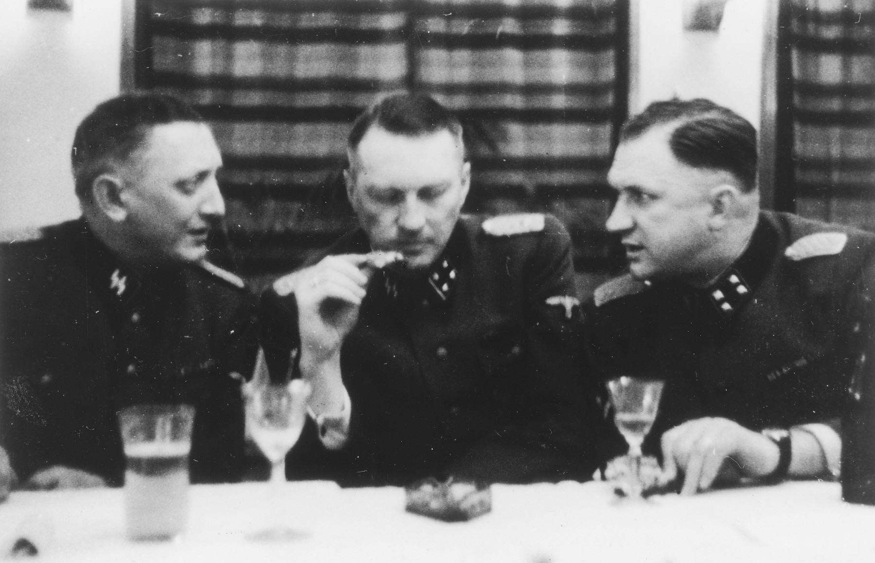 "Three SS officers gather for drinks in a hunting lodge.  From left to right are Franz Xaver, Joachim Caeser and Richard Baer.  The original caption reads ""Jadgesellschaft"" (hunting party)."