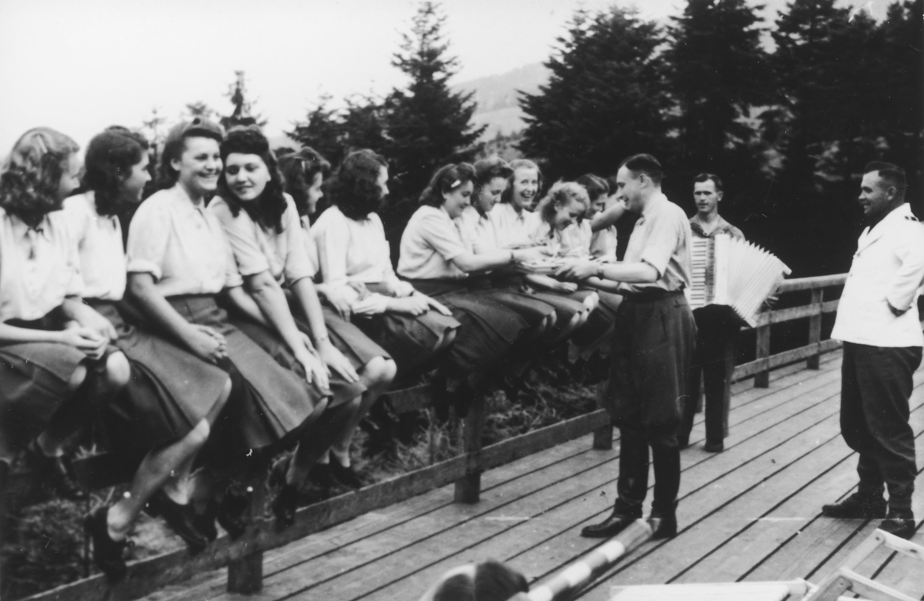 "Members of the SS Helferinnen (female auxiliaries) sit on a fence railing in Solahuette as Karl Hoecker passes out bowls of blueberries.  In the background is a man playing the accordion.   The original caption reads ""Hier gibt es Blaubeeren"" (there are blueberries here)."