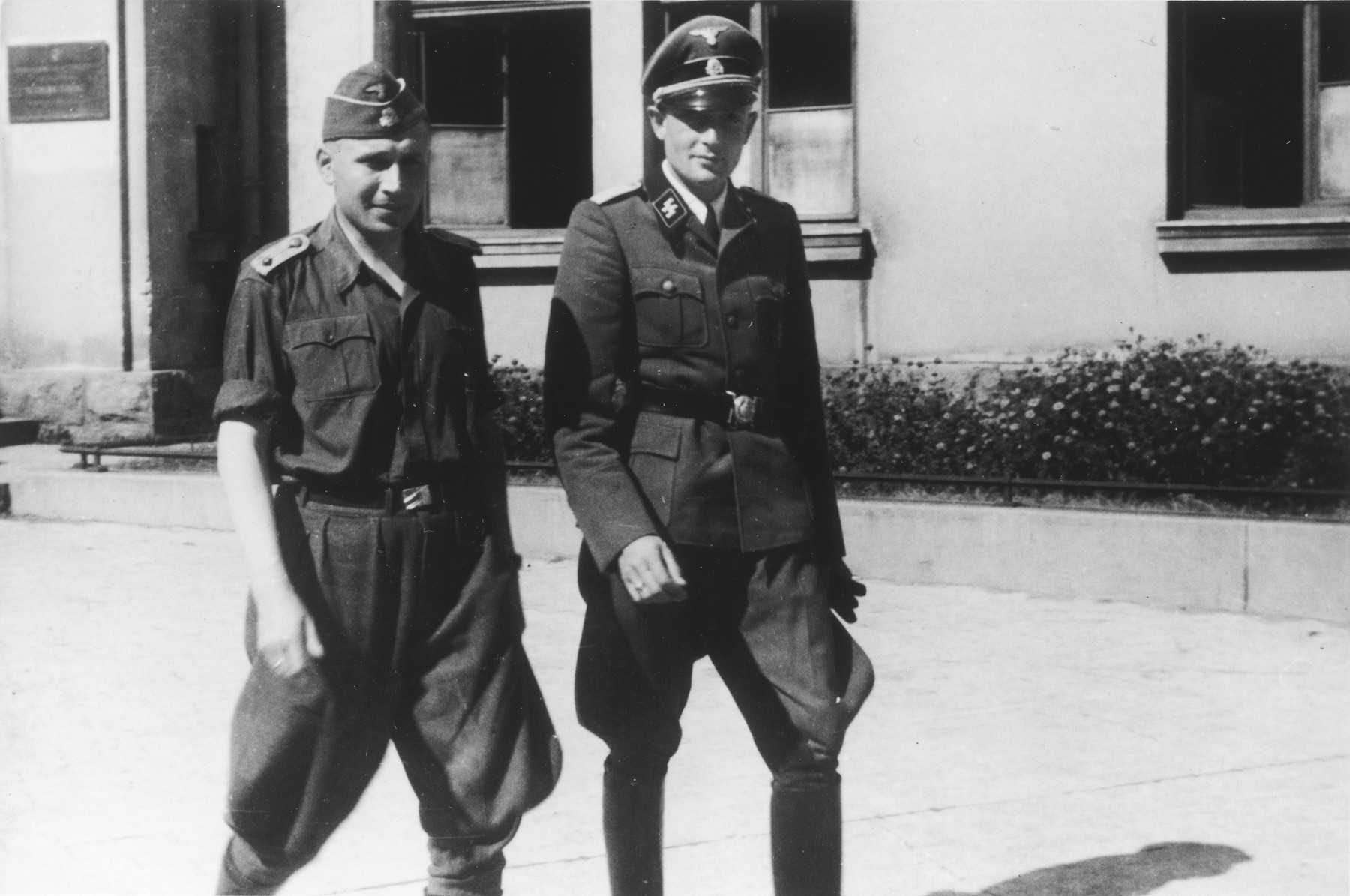 "Two SS officers walk together past a building.  The original caption reads ""Nach der Ausfahrt"" (after the outing [exiting the mine]).  Pictured on the left is Karl Hoecker.  The officer on the right is unidentified (possible Dr, Hans Delmonte)."