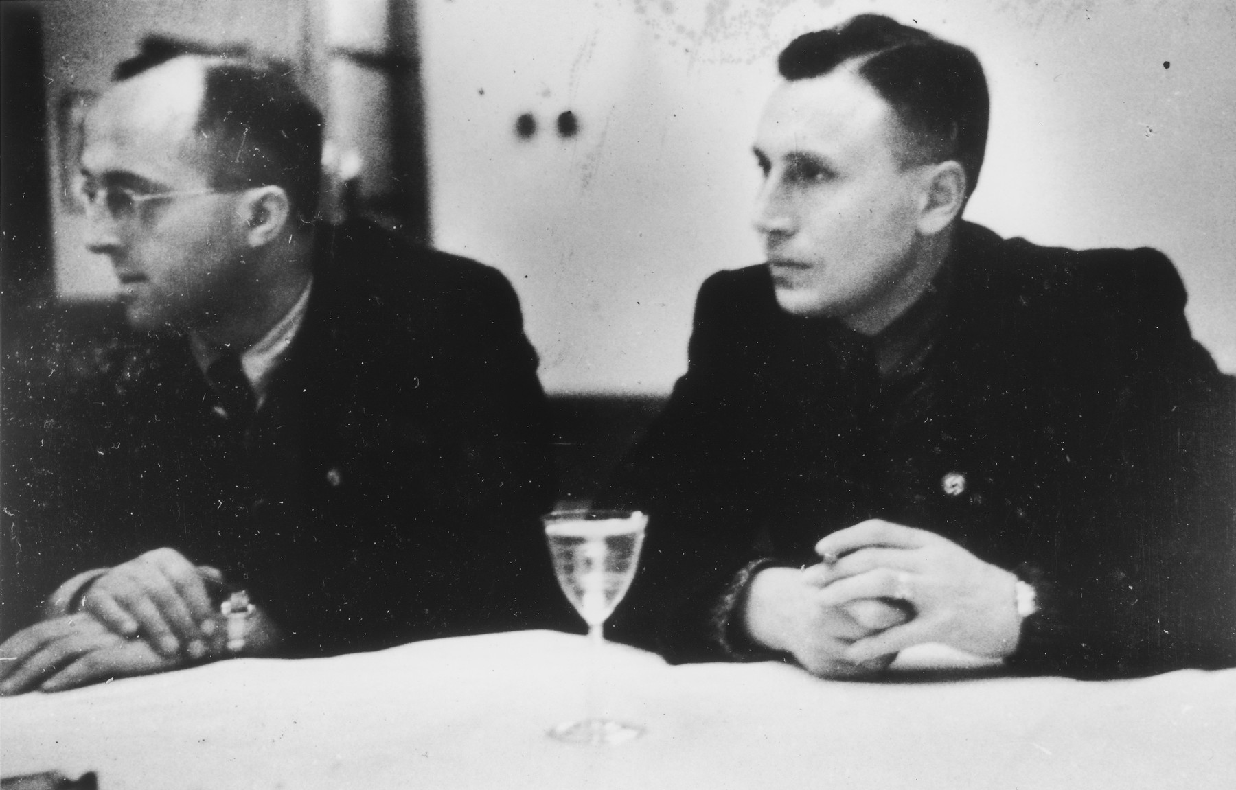 "SS officers gather for drinks in a hunting lodge.  Pictured on the right is Karl Hoecker.  The original caption reads ""Jagdgesellschaft"" (hunting party)."