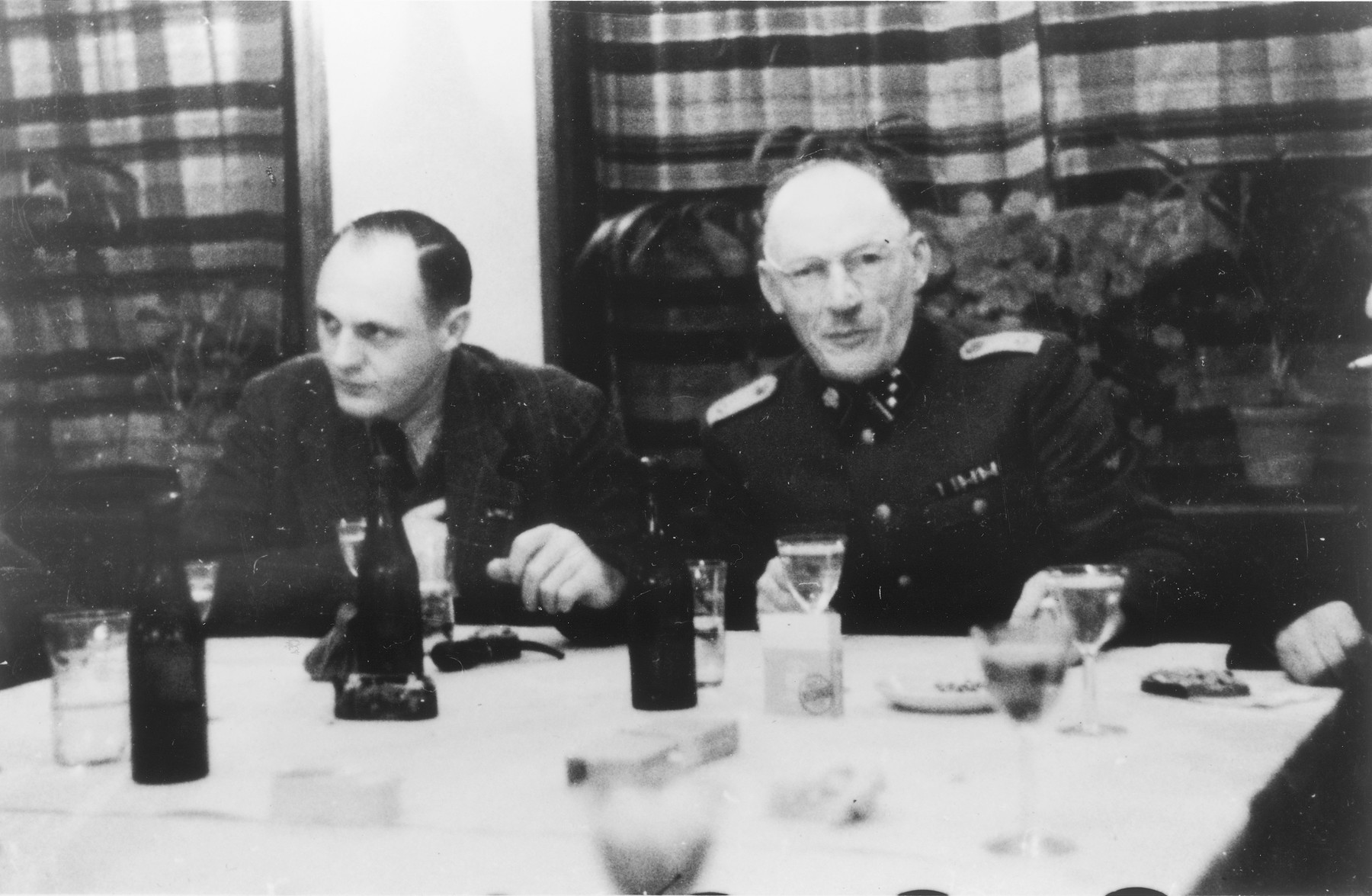 Two SS officers gather for drinks in a hunting lodge.  From left to right are Dr. Eduard Wirths and Heinrich Josten.