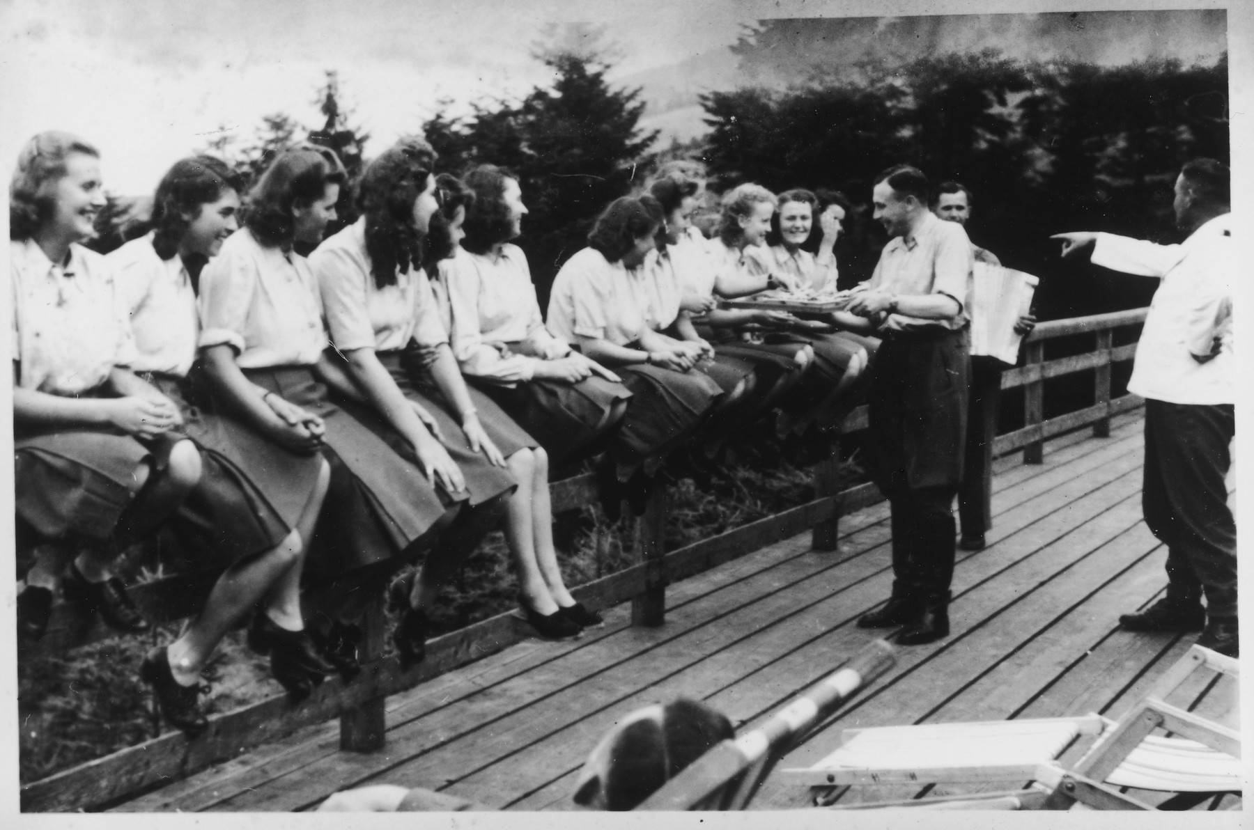 "Members of the SS Helferinnen (female auxiliaries) sit on a fence railing in Solahuette as Karl Hoecker passes out bowls of blueberries.  The original caption reads ""Hier gibt es Blaubeeren"" (there are blueberries here)."