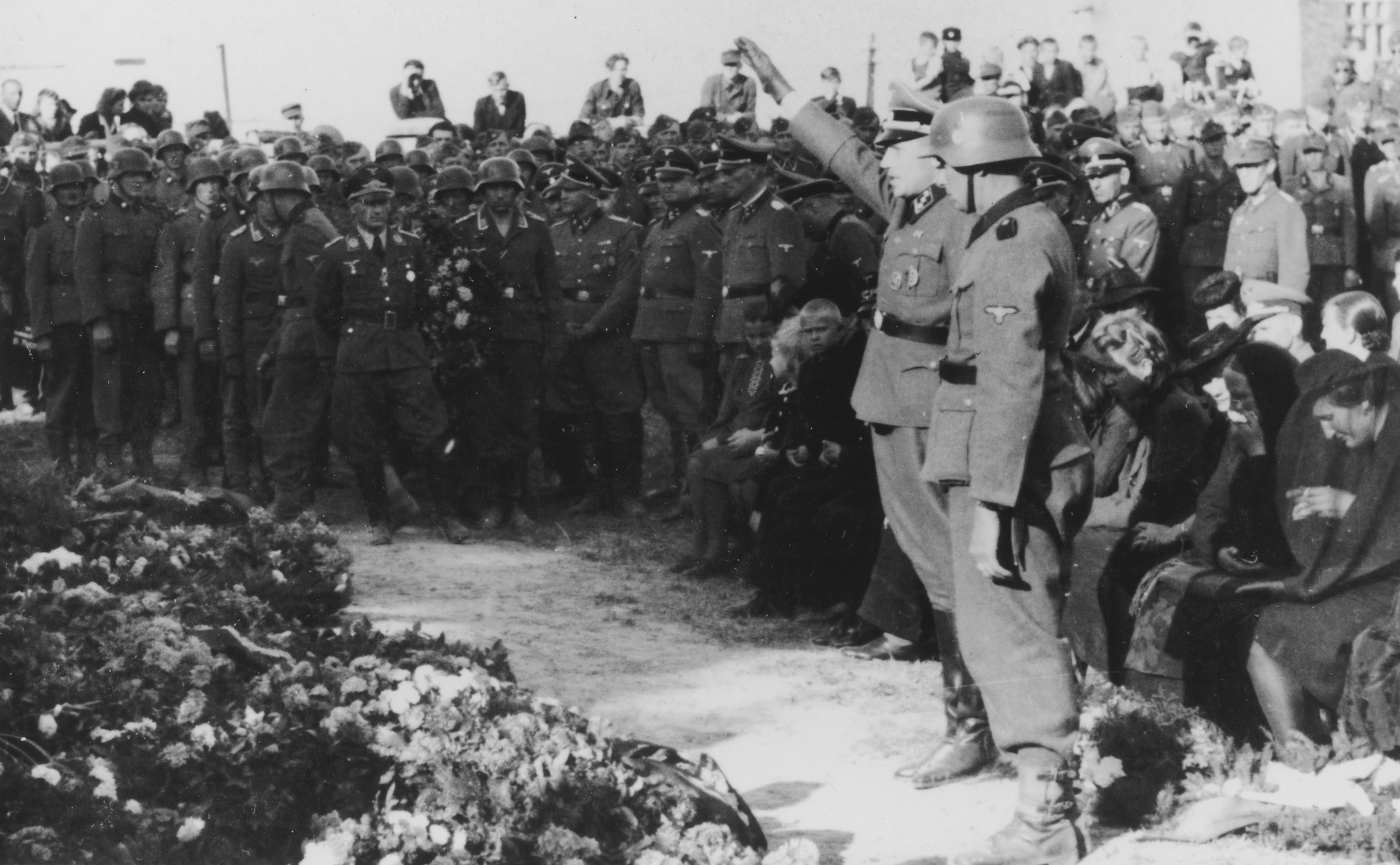 """SS officer, Karl Hoecker salutes in front of an array of wreaths during a military funeral near Auschwitz.  The original caption reads """"Beisetzung von SS Kameraden nach einem Terrorangriff.""""  (Burying our SS comrades from a terror attack.)   This probably is the aftermath of the September 13th bombing of IG Farben in which 15 SS men died in the SS residential blocks and 28 were seriously wounded.  Pictured in the background are Josef Kramer and Karl Moeckel."""