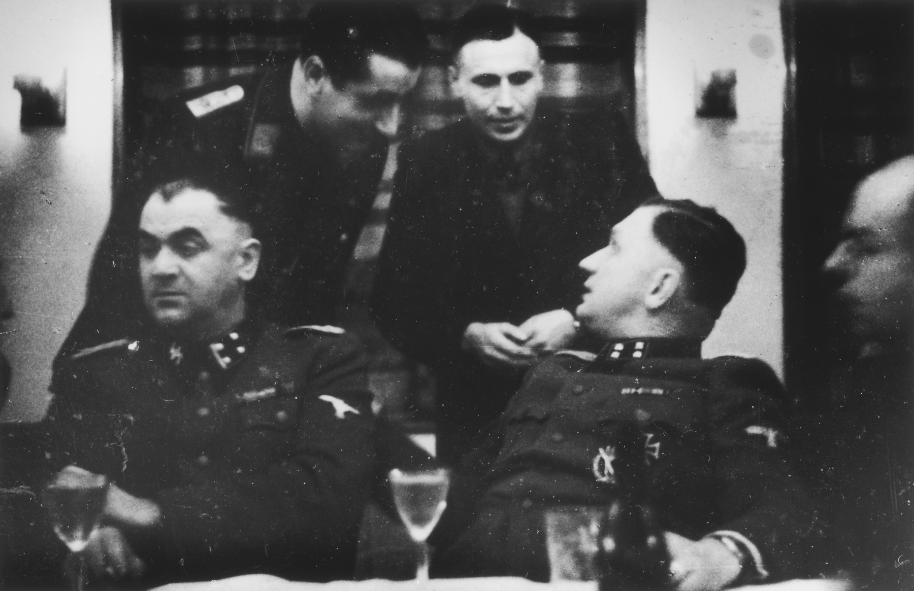 "SS officers gather for drinks in a hunting lodge.  Seated left to right are Karl Moeckel and Richard Baer.  Karl Hoecker is standing between them.  The original caption reads ""Jagdgesellschaft"" (hunting party)."
