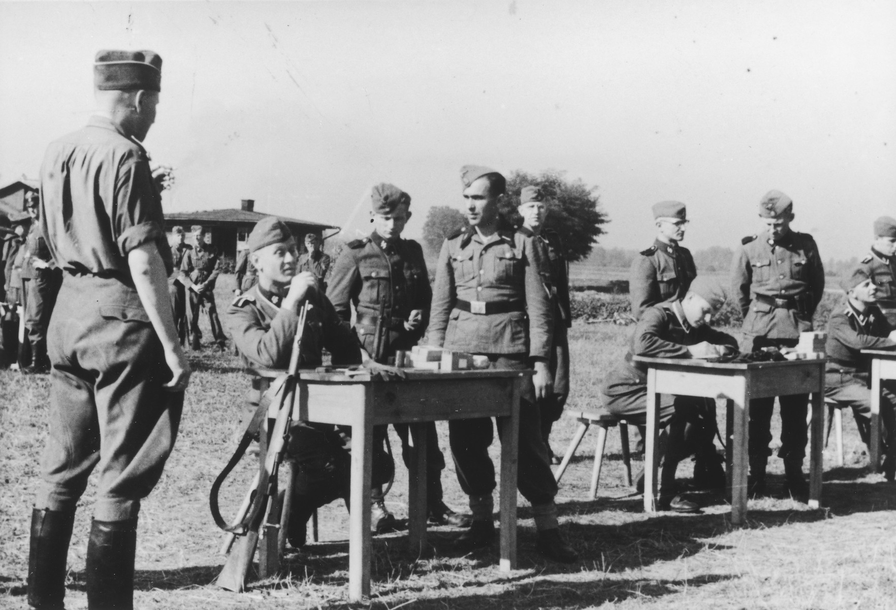 "SS officers gather for shooting practice. On the far left is Karl Hoecker(with his back to camera).  The original caption reads ""Auf dem Schiessstand"" (at the firing range)."
