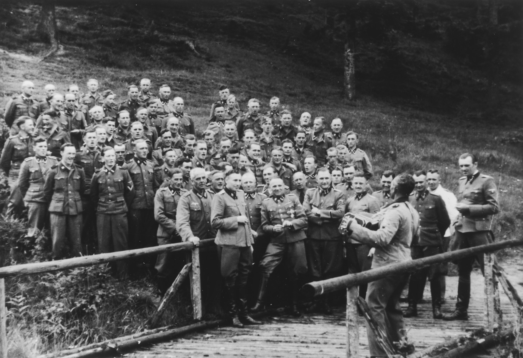 An accordionist leads a sing-along for SS officers at their retreat at Solahuette outside Auschwitz.  Pictured in the front row are Karl Hoecker, Otto Moll, Rudolf Hoess, Richard Baer, Josef Kramer (standing slightly behind Hoessler and partially obscured), Franz Hoessler, Josef Mengele, Anton Thumann, and Walter Schmidetzki.  Hermann Buch is in the center.  Konrad Wiegand, head of the Fahrbereitschaft (car and truck pool) is in the middle.  [Based on the officers visiting Solahutte, we surmise that the photographs were taken to honor Rudolf Hoess who completed his tenure as garrison senior on July 29.]