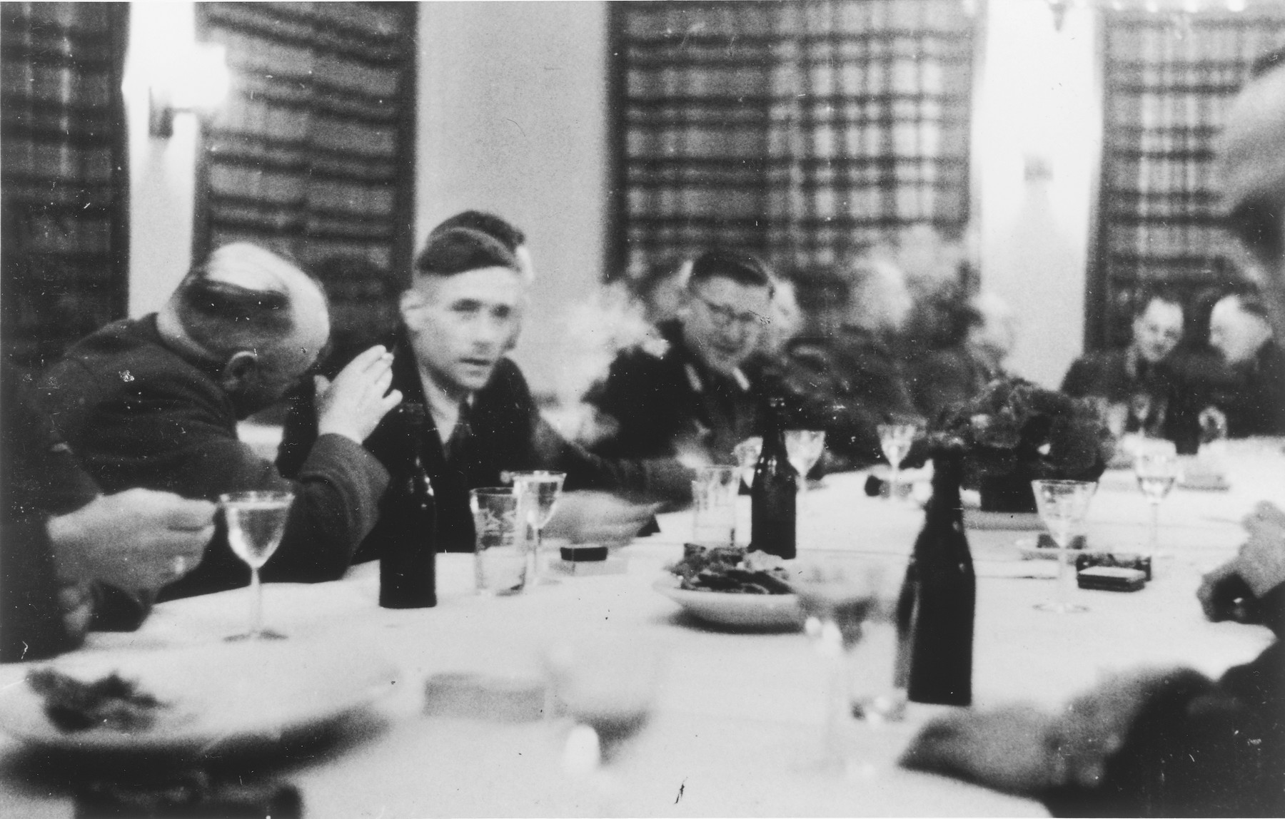 SS officers gather for drinks in a hunting lodge.  Among those pictured is Heinrich Josten (head of the table, right).