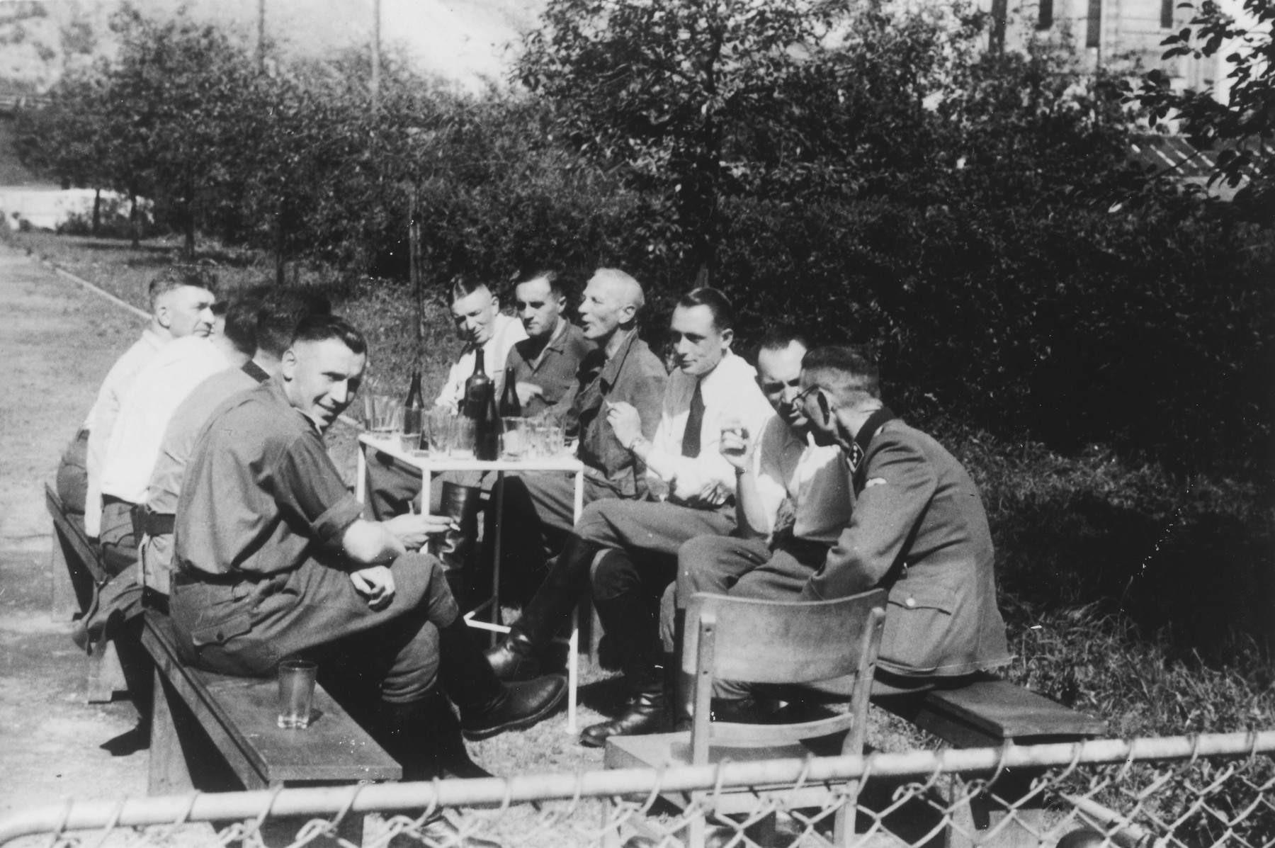 "SS officers, including several SS physicians, sit around a table drinking probably following a visit to coal mine.    The original caption reads ""Nach der Ausfahrt"" (after the outing [exiting the mine]).  Among those pictured are Karl Hoecker (far left), Dr. Fritz Klein (left hand side, end of table), Gerhard Gerber (right, third from front), Dr. Enno Lolling (four from front),  Alfred Trzebinski, and Dr. Willi Schatz (right side, end)."