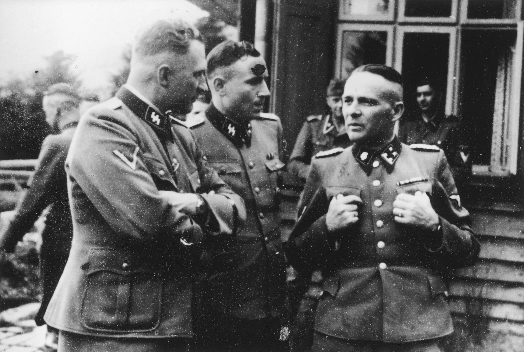 Three SS officers chat on the grounds of the SS retreat, Solahuette, outside of Auschwitz.  From left to right: Richard Baer (commandant of Auschwitz), Karl Hoecker (his adjutant), and Rudolf Hoess (the former commandant).  [Based on the officers visiting Solahutte, we surmise that the photographs were taken to honor Rudolf Hoess who completed his tenure as garrison senior on July 29.]